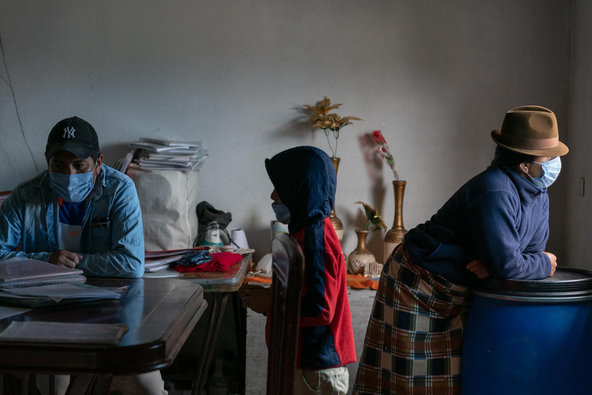 """Rodrigo Cela (34) accompanies his children while they do their homework. María Blanca Quishpe (35) looks out the window to see what happens in the neighborhood. Maycol Cela (11) and Verónica Cela (12) are elementary students of the Yachay Wasi Intercultural Bilingual Community School. Located south of Quito, in Ecuador. They live with their older brother Jonathan Cela (14), their mother María Blanca Quishpe (35) and their father Rodrigo Cela (34). At home they do not have an Internet connection and have only a smart phone in which they do not always have data. The school delivers in print form (at the school door) the weekly homework schedule for families who do not have an Internet connection, and teachers follow up through phone calls. They live near their school, in the """"Monjas"""" neighborhood. Her mother works at home and Rodrigo works as a bricklayer. The Covid19 pandemic has affected them tremendously, they have almost no money to buy food. The principals of the Yachay Wasi school invited them to work on the last harvest of their crops so that they can have a small economic income. Photographer: Ana Maria Buitron. Quito, Ecuador. Rodrigo Cela (34) acompaña a sus hijos mientras hacen los deberes. María Blanca Quishpe (35) mira por la ventana a ver qué pasa en el barrio. Maycol Cela (11) y Verónica Cela (12) son estudiantes de primaria de la Escuela Comunitaria Intercultural Bilingüe Yachay Wasi. Ubicada al sur de Quito, en Ecuador. Viven con a su hermano mayor Jonathan (14), su madre María Blanca Quishpe (35) y su padre Rodrigo Cela (34). En casa no tienen conexión a Internet y tienen solo un celular inteligente en el cual no siempre tiene datos. La escuela entrega de forma impresa (en la puerta de la escuela) la programación semanal de tareas, para las familias que no tienen Internet, y los profesores dan seguimiento a través de llamadas telefónicas. Viven cerca de su escuela, en el barrio """"Monjas"""". Su madre trabaja en las labore"""