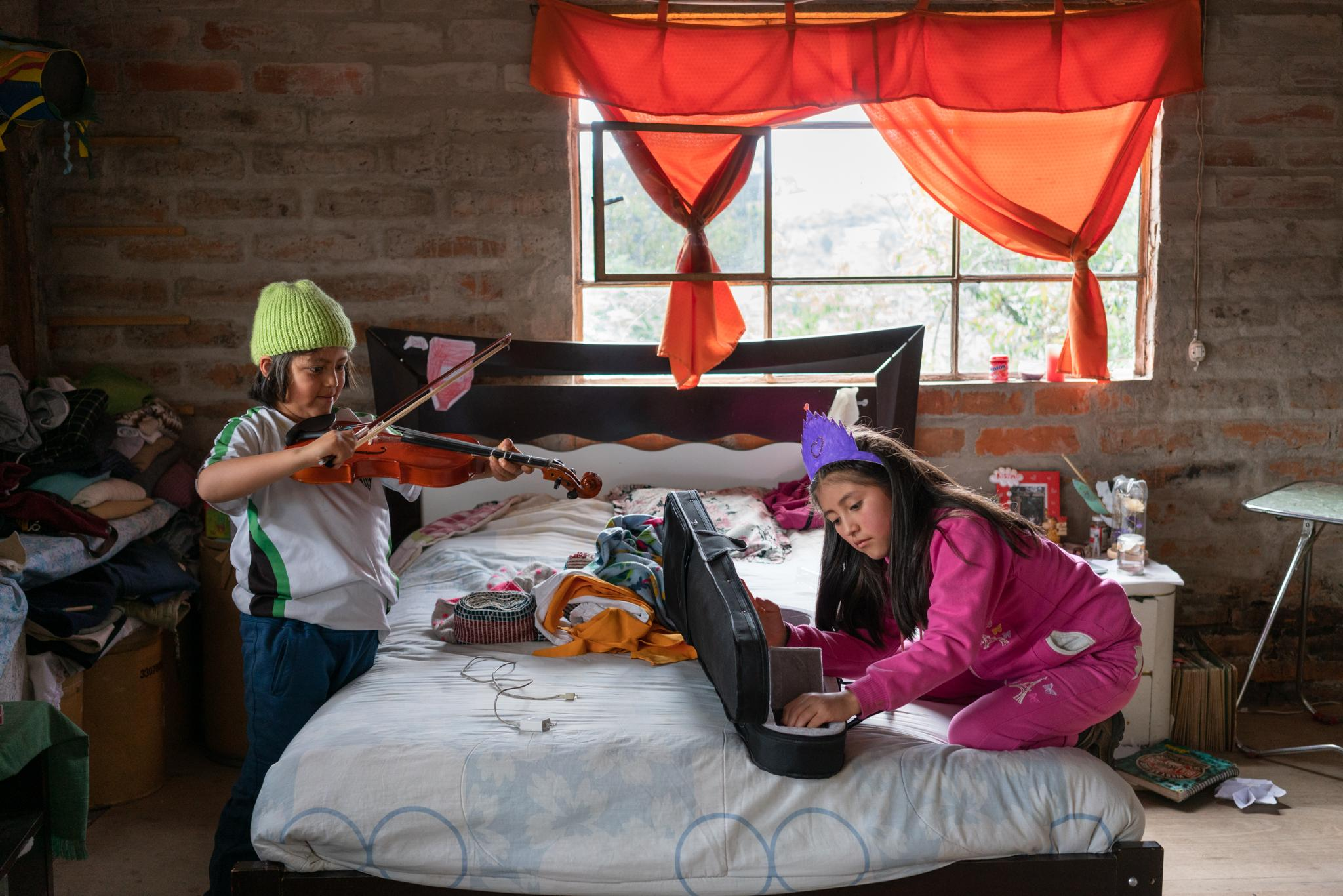 Jasid plays the violin that his parents recently bought for his sister Suri. Parents comment that they have made a financial effort to give this gift to Suri. Jasid Taquiri Aguayo (7) and Suri Laina Aguayo (10) are elementary school students of the Yachay Wasi Intercultural Bilingual Community School. Located south of Quito in Ecuador. They live with her sister Arelí (14), her mother Dina Taco (39) and her father Juan Andrés Aguayo (34). They live in a big house, their grandparents are their neighbors, and they have a big garden full of plants and some trees. Her parents say that at the beginning of the quarantine it was more fun for the children, but nowadays they are missing going to school and sharing with their classmates. Dina studies Infant Education at distance, this has given her tools to closely accompany her children's studies during the confinement. She has created routines for children to make better use of time; at 8:30 they do exercises and dance in the patio, until 11:30 they do their homework, then they play and they also collaborate in certain household responsibilities. They are a family with limited financial resources, the Covid19 has left the parents without work, however, they can have the support of the grandparents. They are a family with a broad vision of social work. Photographer: Ana Maria Buitron. Quito, Ecuador. Jasid toca el violín que sus padres le compraron hace poco a su hermana Suri. Los padres comentan que han hecho un esfuerzo económico para darle este regalo a su hija. Jasid Taquiri Aguayo (7) y Suri Laina Aguayo (10) son estudiantes de primaria de la Escuela Comunitaria Intercultural Bilingüe Yachay Wasi. Ubicada al sur de Quito en Ecuador. Viven con su hermana Arelí (14), su madre Dina Taco (39) y su padre Juan Andrés Aguayo (34). Viven en una casa grande, sus abuelos son sus vecinos y tienen un jardín grande lleno de planta y algunos árboles. Sus padres cuentan que al inicio de la cuarentena era más divertido