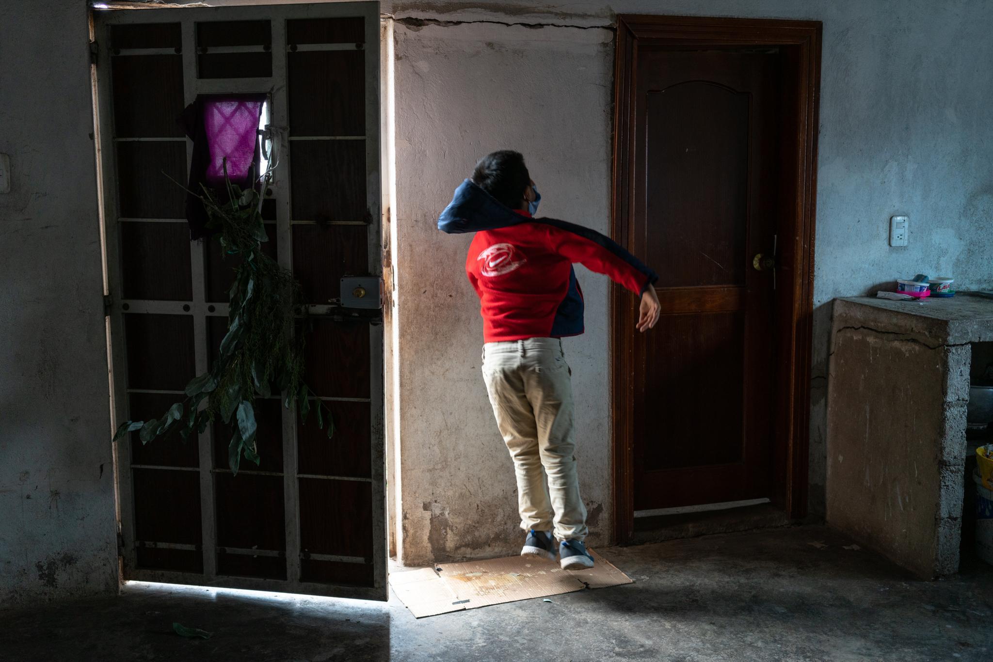 """Maycol Cela (11) plays and jumps before leaving home. Maycol Cela (11) and Verónica Cela (12) are elementary students of the Yachay Wasi Intercultural Bilingual Community School. Located south of Quito, in Ecuador. They live with their older brother Jonathan Cela (14), their mother María Blanca Quishpe (35) and their father Rodrigo Cela (34). At home they do not have an Internet connection and have only a smart phone in which they do not always have data. The school delivers in print form (at the school door) the weekly homework schedule for families who do not have an Internet connection, and teachers follow up through phone calls. They live near their school, in the """"Monjas"""" neighborhood. Her mother works at home and Rodrigo works as a bricklayer. The Covid19 pandemic has affected them tremendously, they have almost no money to buy food. The principals of the Yachay Wasi school invited them to work on the last harvest of their crops so that they can have a small economic income. Photographer: Ana Maria Buitron. Quito, Ecuador. Maycol Cela (11) salta como un juego antes de salir de la casa. Maycol Cela (11) y Verónica Cela (12) son estudiantes de primaria de la Escuela Comunitaria Intercultural Bilingüe Yachay Wasi. Ubicada al sur de Quito, en Ecuador. Viven con a su hermano mayor Jonathan (14), su madre María Blanca Quishpe (35) y su padre Rodrigo Cela (34). En casa no tienen conexión a Internet y tienen solo un celular inteligente en el cual no siempre tiene datos. La escuela entrega de forma impresa (en la puerta de la escuela) la programación semanal de tareas, para las familias que no tienen Internet, y los profesores dan seguimiento a través de llamadas telefónicas. Viven cerca de su escuela, en el barrio """"Monjas"""". Su madre trabaja en las labores del hogar y Rodrigo trabaja como albañil. La pandemia por el Covid19 les ha afectado muchísimo a nivel económico. Casi no tienen dinero para comprar comida. Los directores de la escuela Ya"""