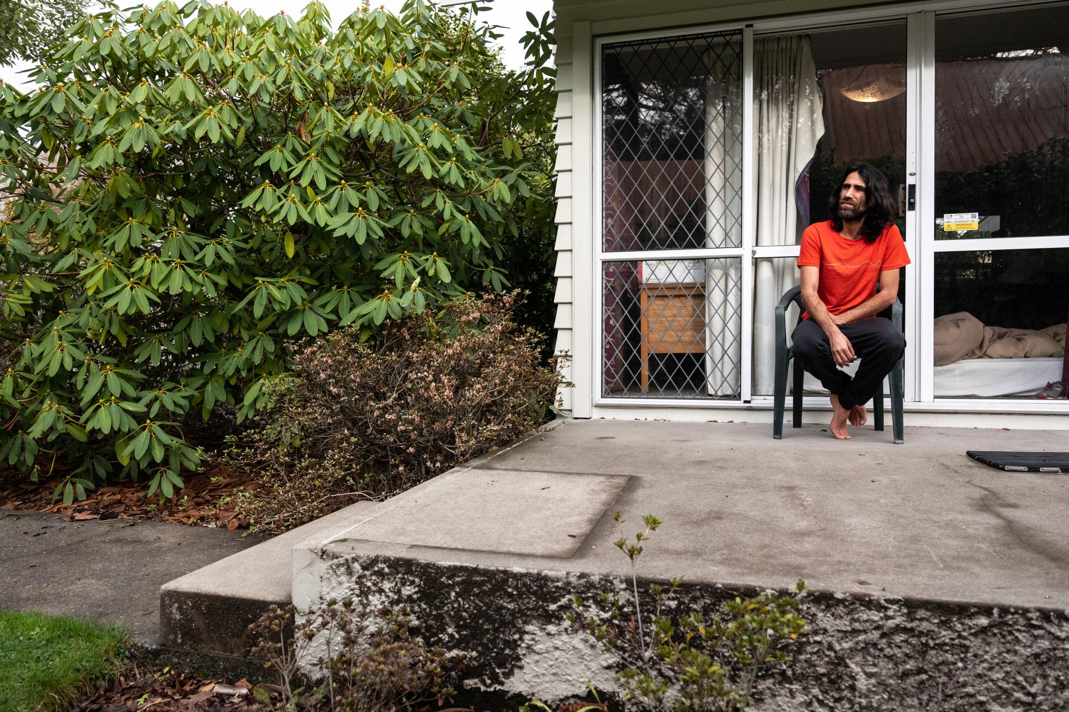 Behrouz Boochani on the back porch outside his house in Christchurch, New Zealand. July 16th, 2020. Birgit Krippner for The New York Times.