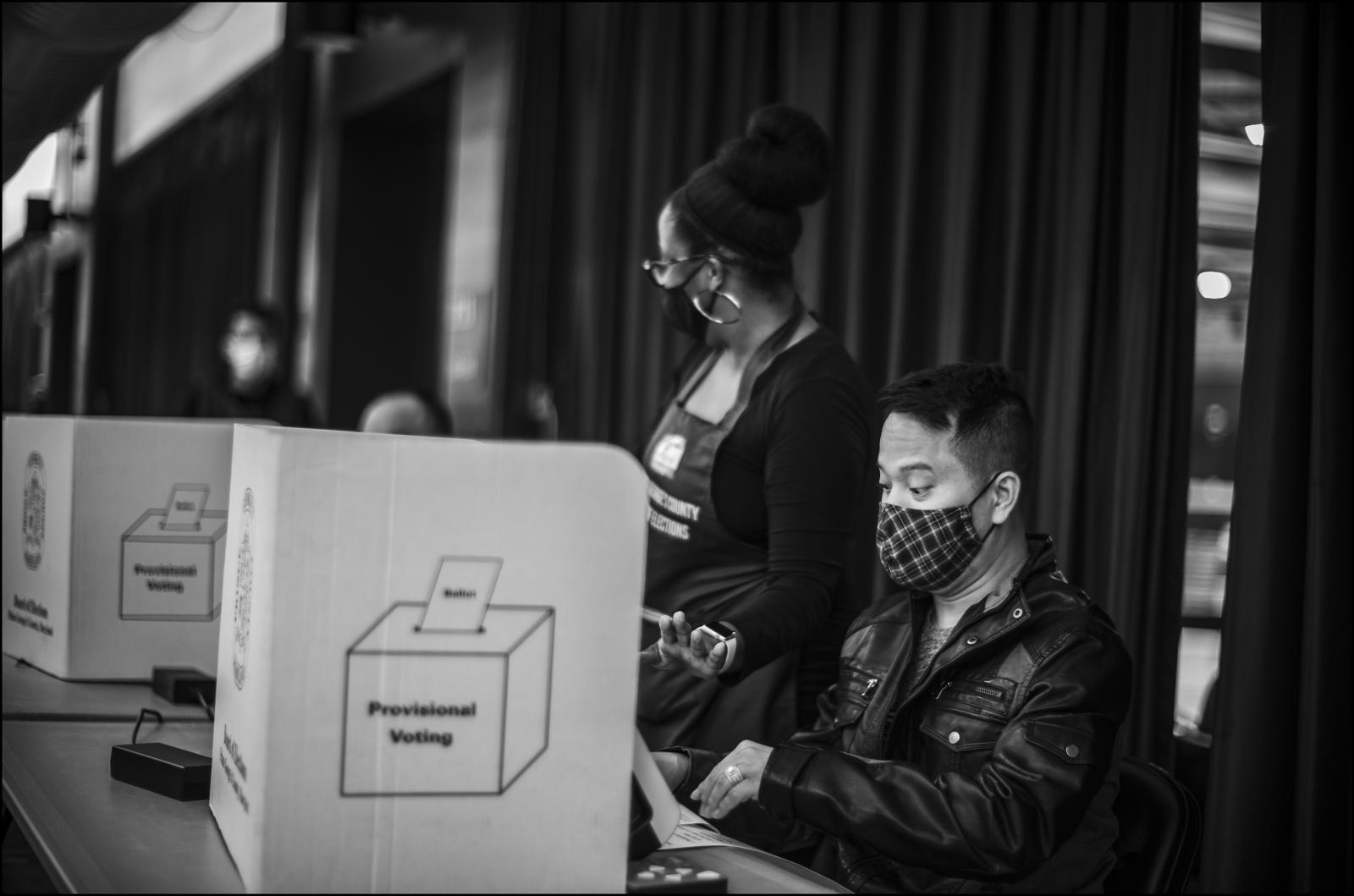 "First time voter, ""Elvid"" an immigrant from Viet Nam casts his ballot during early voting (11/02/20). He was voting at Upper Marlboro (MD) Equestrian Center. In back,election polling worker Ashley Owens. Prince George's County, MD."