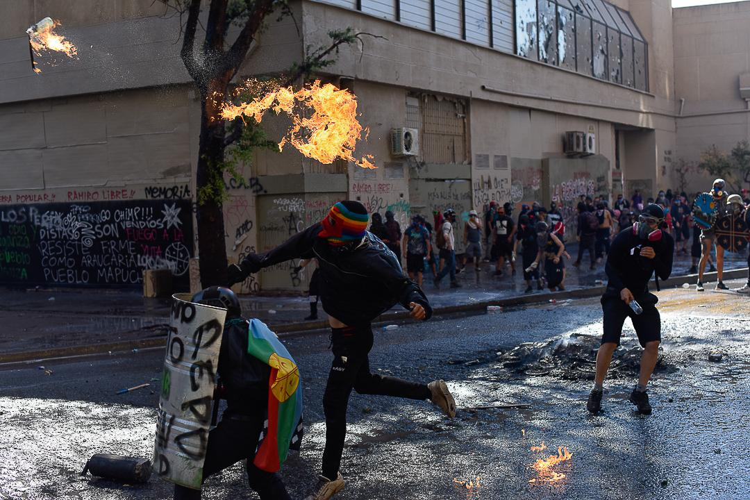 A hooded demonstrator throws a Molotov cocktail bomb at carabineros in response to repression by the authorities.