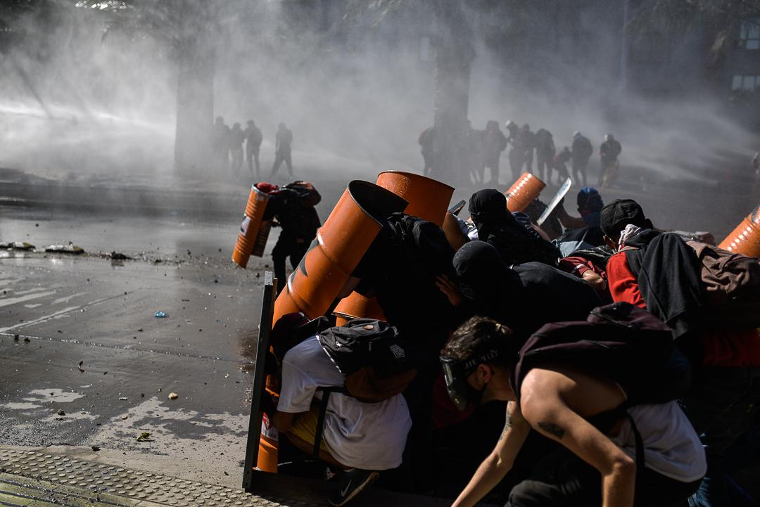 hundreds of demonstrators protect themselves with handmade shields to face shotgun fire with pellets and tear gas grenades. more than 300 people have suffered eye trauma as a result of carabineros shooting without following protocol.