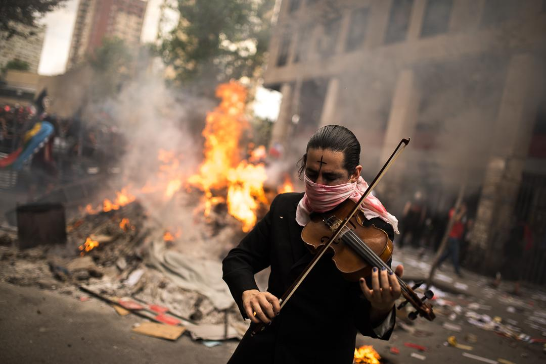 A musician plays his violin in the middle of the barricades to encourage the demonstrators before the clashes with the police,