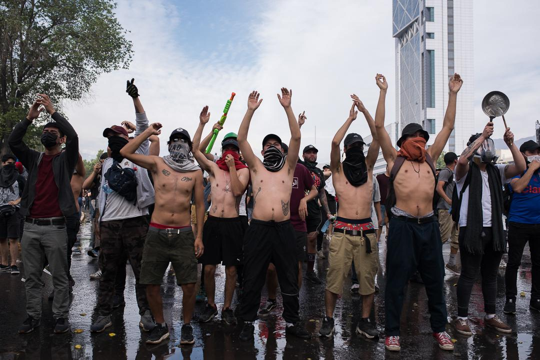 hundreds of protesters gather in different parts of Santiago to inflict improvements in the constitution and resignation of President Sebastian. octuber 22. 2019.protesters raise their hands so as not to be assaulted by police