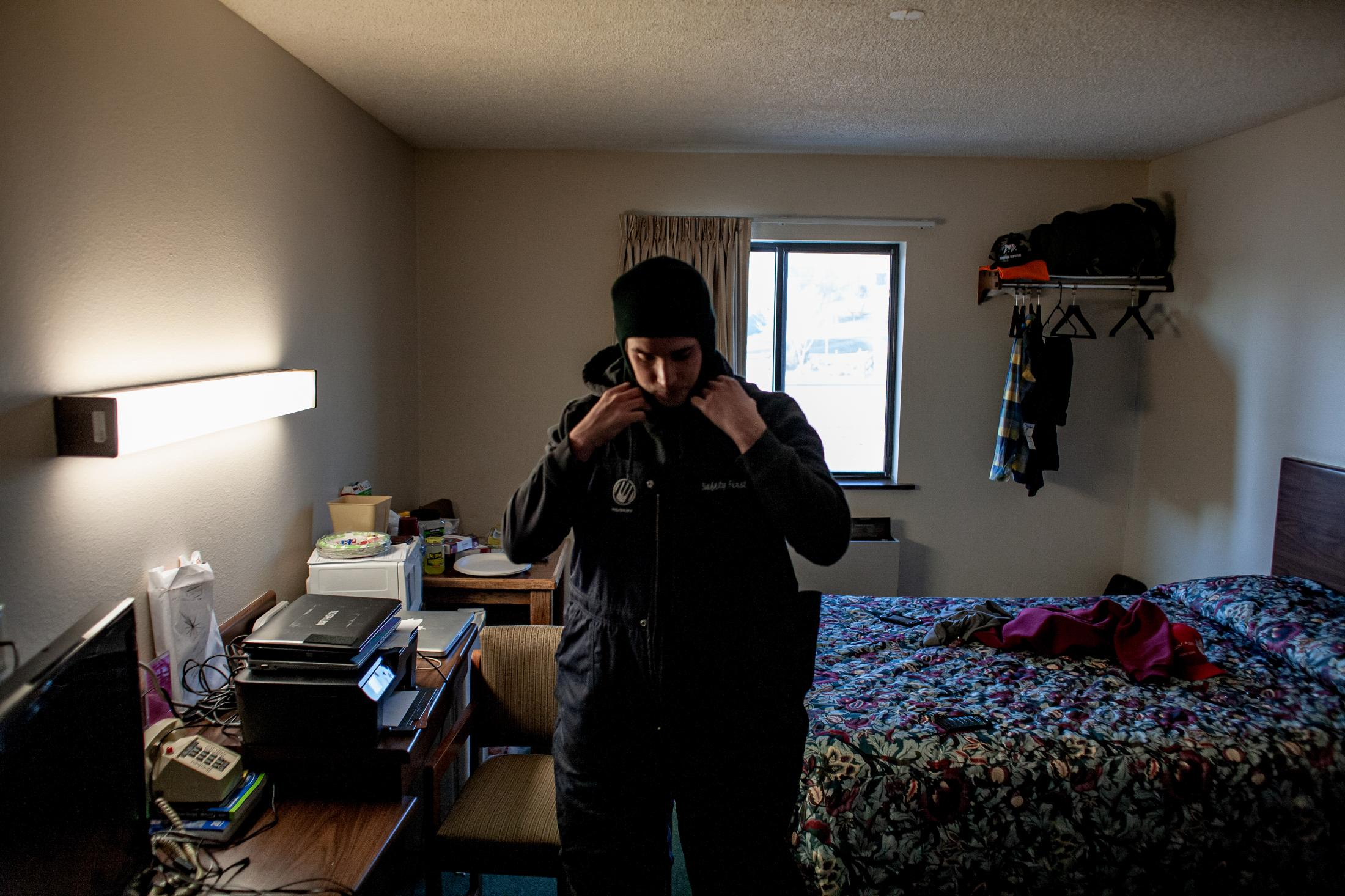 """2/6/14- North Dakota - A phone call awakens Adam Braum that more trucks will be coming to him to fill with frac sand. Adam must put on three layers of clothing to protect himself from the cold weather and winds. """"I have nightmares about the cell phone; I have only gotten two hours of sleep."""""""