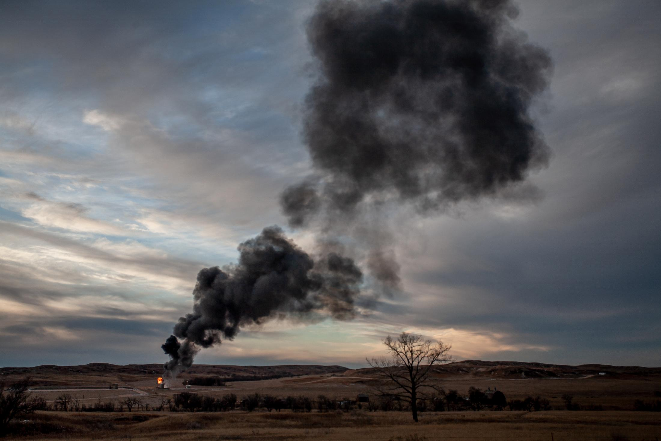 2/7/14- North Dakota - Smoke shoots to the sky from a natural gas flame that has been flooded with oil. Well sights that have pump jacks on them are inspected and emptied daily, but things go wrong with the land's extreme conditions.