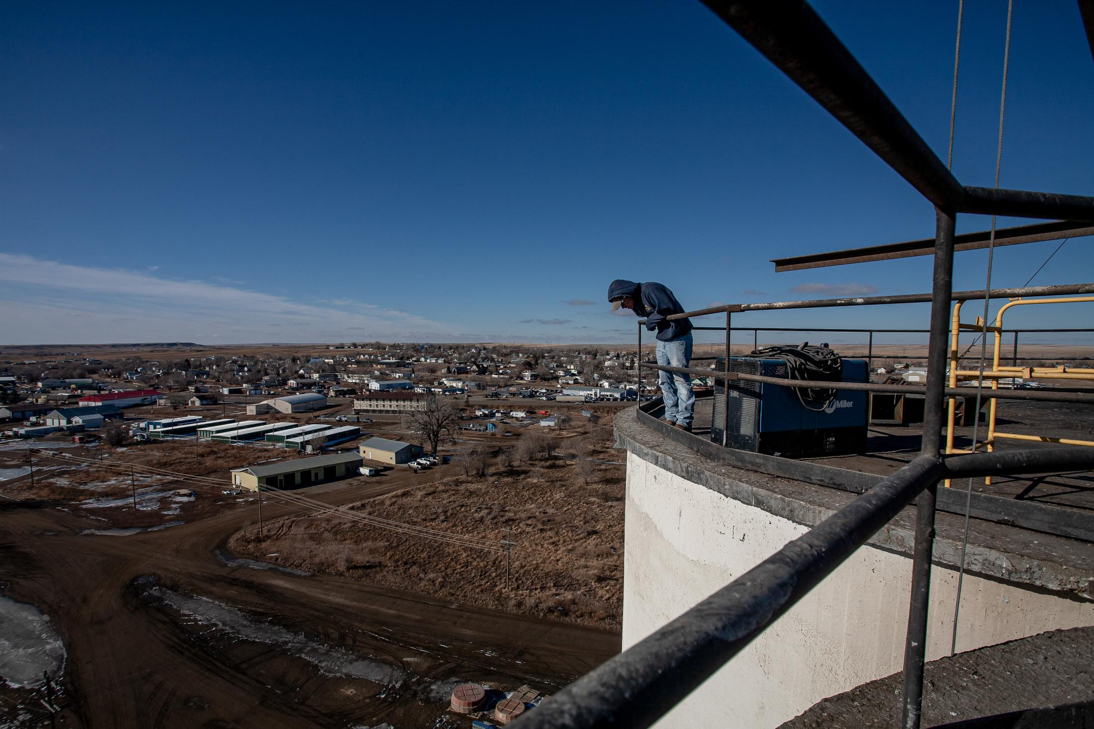 2/20/14- North Dakota - A Sioux grain worker looks down from a grain silo next door to a frac sand storage lot. With little opportunities on the Wolf Point reservation, oil field work is a desired occupation.