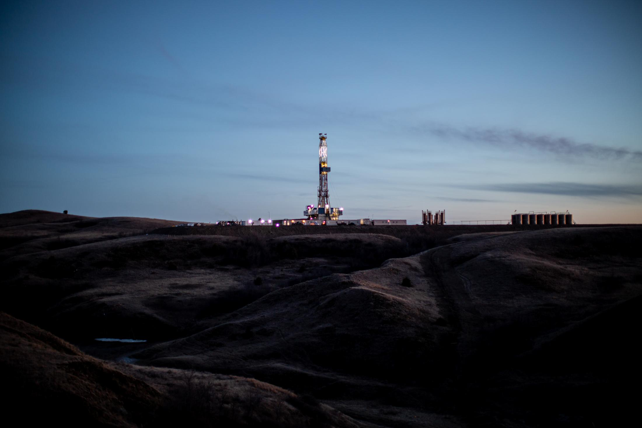 4/7/15- North Dakota - A derick stands in the middle of a rural field; the dericks are used to drill and push casing pipes deep into the ground to pump oil.