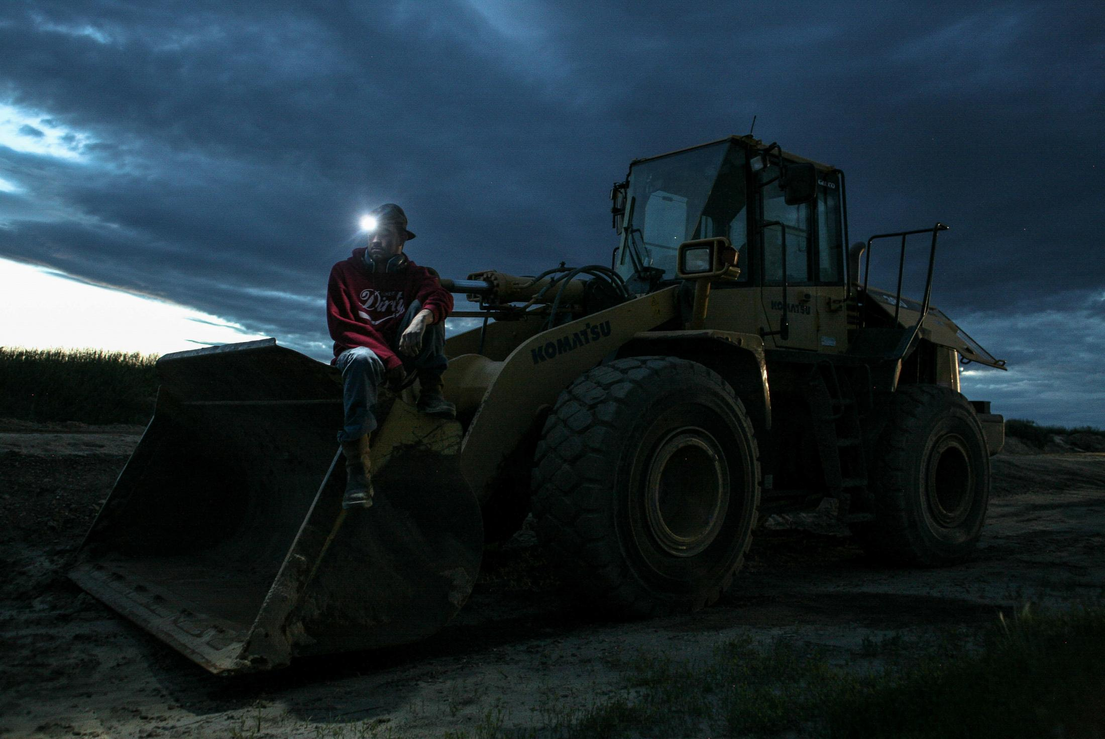6/20/14- North Dakota - Dylan, an operator at a frac sand storage facility, sits on a front-end loader's bucket. Dylan moved from Louisiana to North Dakota to find opportunities for himself, as many young men have.