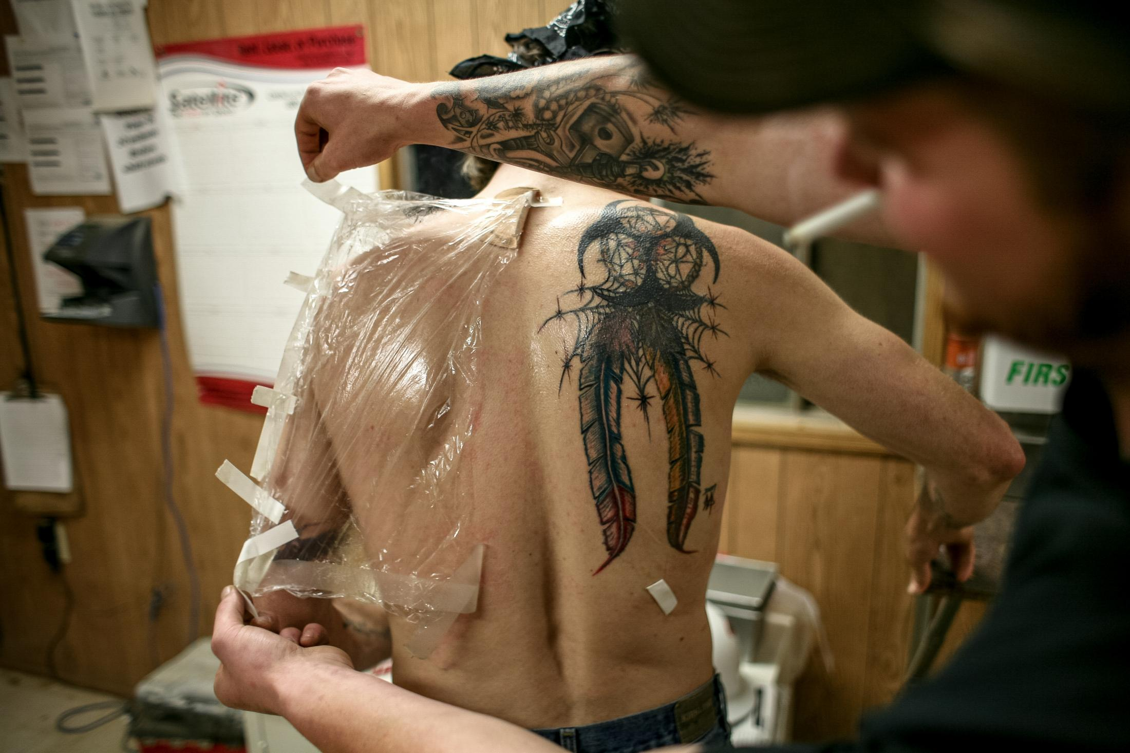 6/20/14- North Dakota - A man removes plastic wrap from a co-worker back, revealing a new tattoo he got in the oil field. Men in The Bakken find themselves discovering more than an opportunity; they discover a brotherhood between workers. The job is hard, the land is unforgiving, but the friendships are strong.