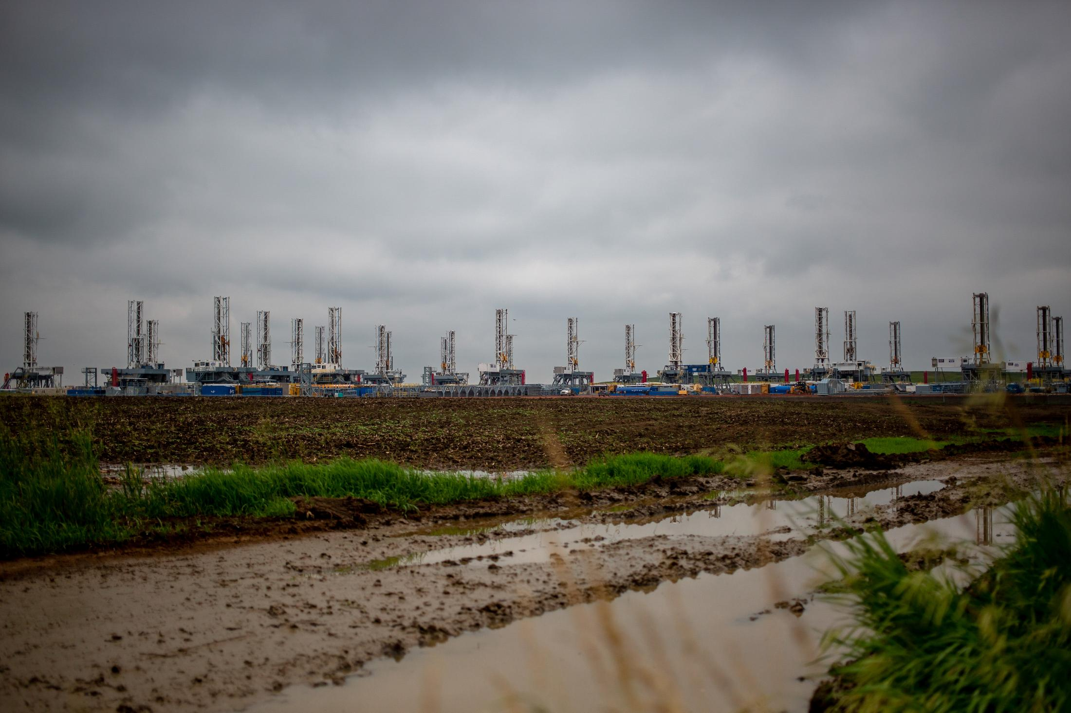 7/1/15- North Dakota - An army of derrick is staged to be transported or stored in the late months of the oil boom. Without warning fracing companies started laying off workers and shutting down production. The price of oil has dropped significantly and cost more to drill than to profit.