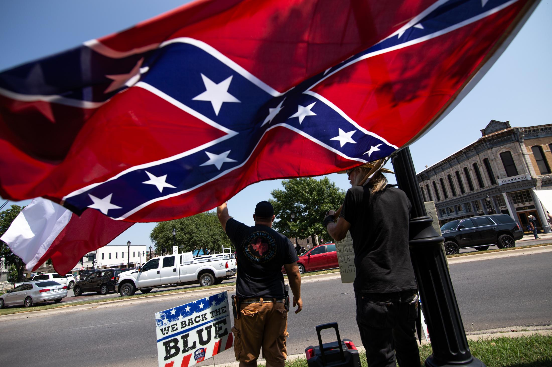 During a demonstration of the Weatherford Confederate monument, that was voted by the city council to not remove from the city courthouse grounds, supporters wave a Confederate flag on the city courthouse's street curb. Motorists drive by and honk at the protestors.