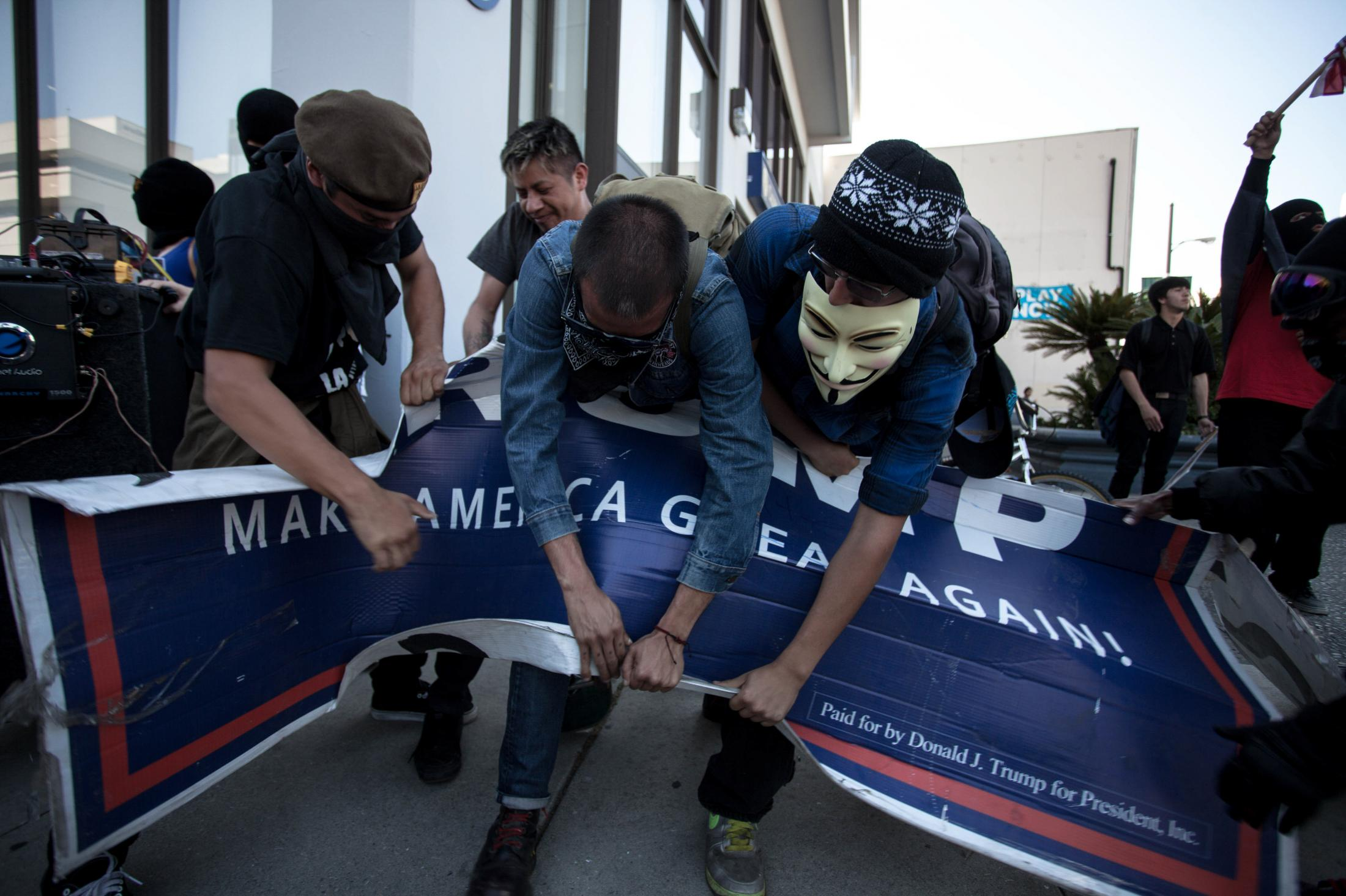 Members of ANTIFA, tear apart a Trump Campaign Sign during a protest on November 4, 2018.