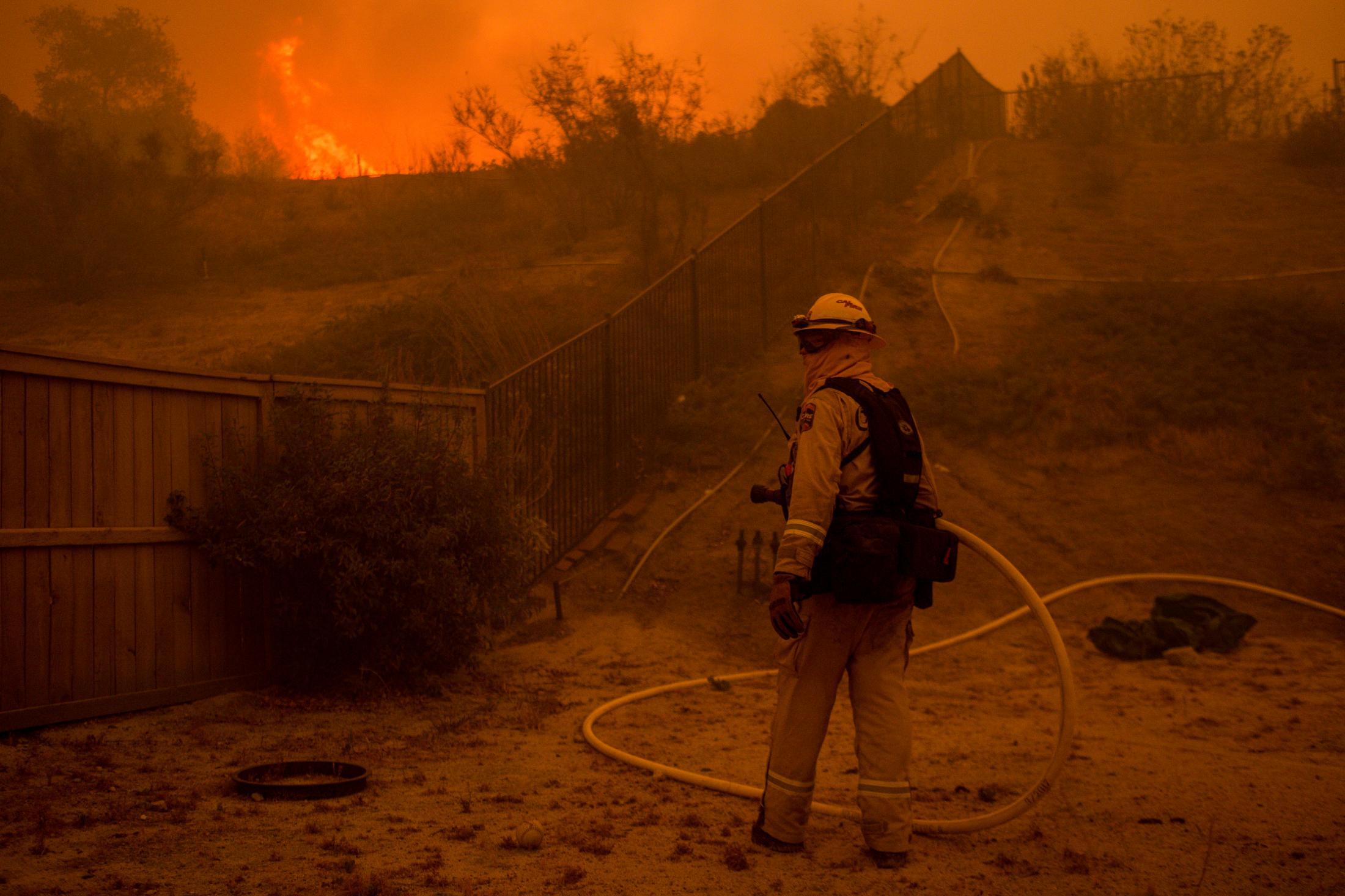 A firefighter carries a house from a fire truck into the backyard of a house, becoming a frontline in the fight of this wildfire.