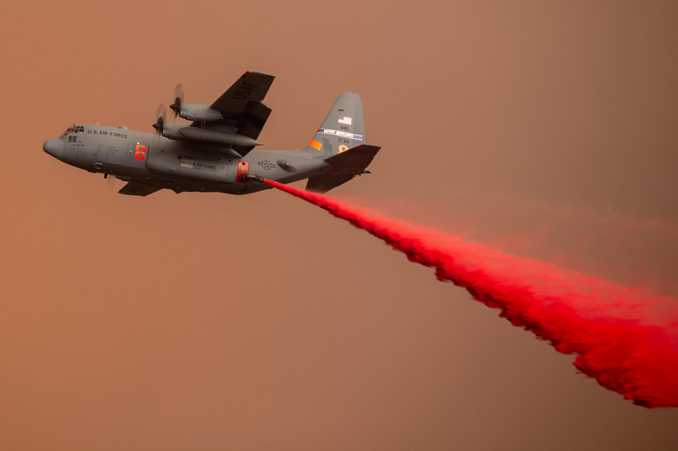 An Air Force C-130 plane drops fire retardant on houses to help protect them from the incoming blaze.