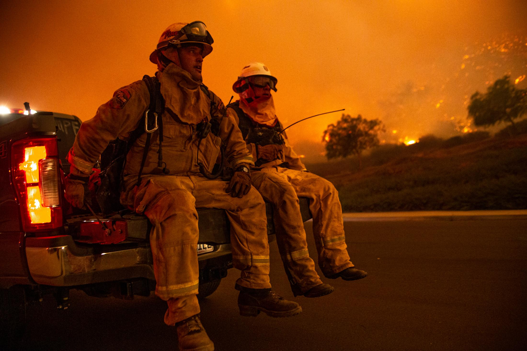 This wildfire burned; 96,949 acres and destroyed 1,643 structures. Three people reported to have died in the blaze, and over a quarter-million evacuated. Two Fire Chiefs sit on the bed of a truck after hours of battling a violent wildfire.