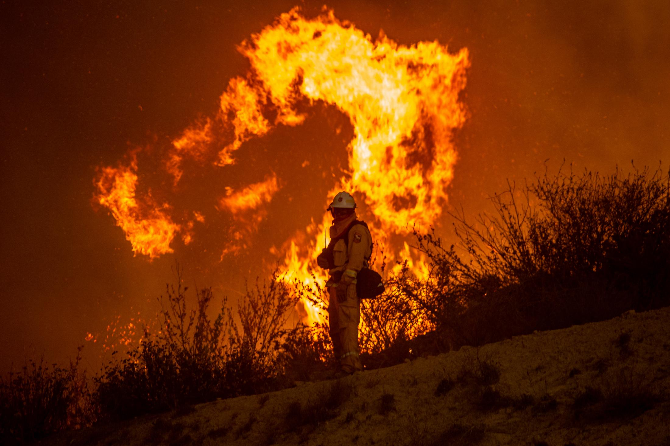 A CALFIRE member stands in front of a bursting flame on the fireline of one of the most dangerous fires in California history.