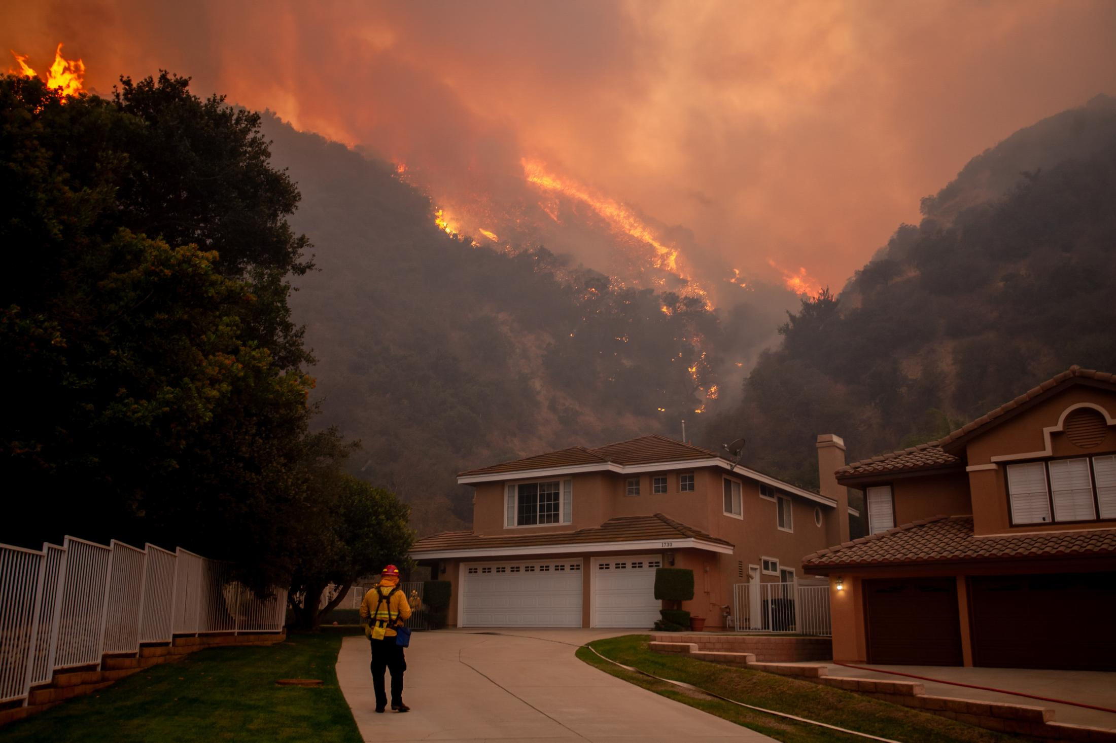 A firefighter moves towards a house that sits on the frontline of a wildfire. Fires move quickly, and as winds pick up, the flames can change directions in seconds.