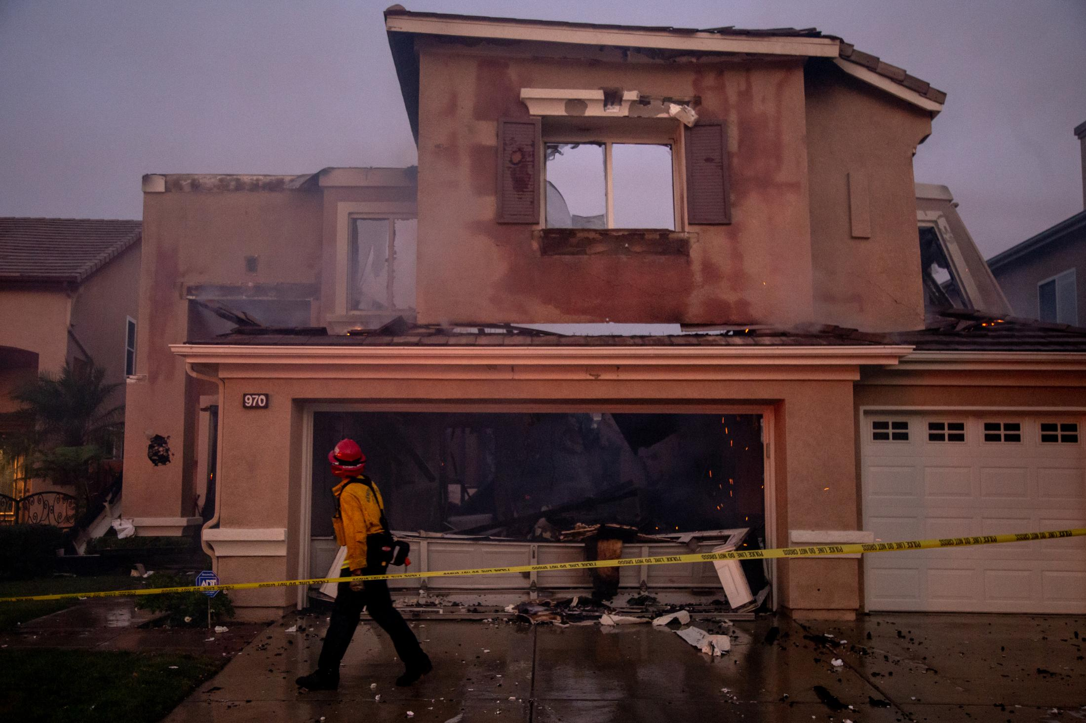 A building is left destroyed after a wildfire spreads through a community. Firefighters tape off any structures that could be dangerous.