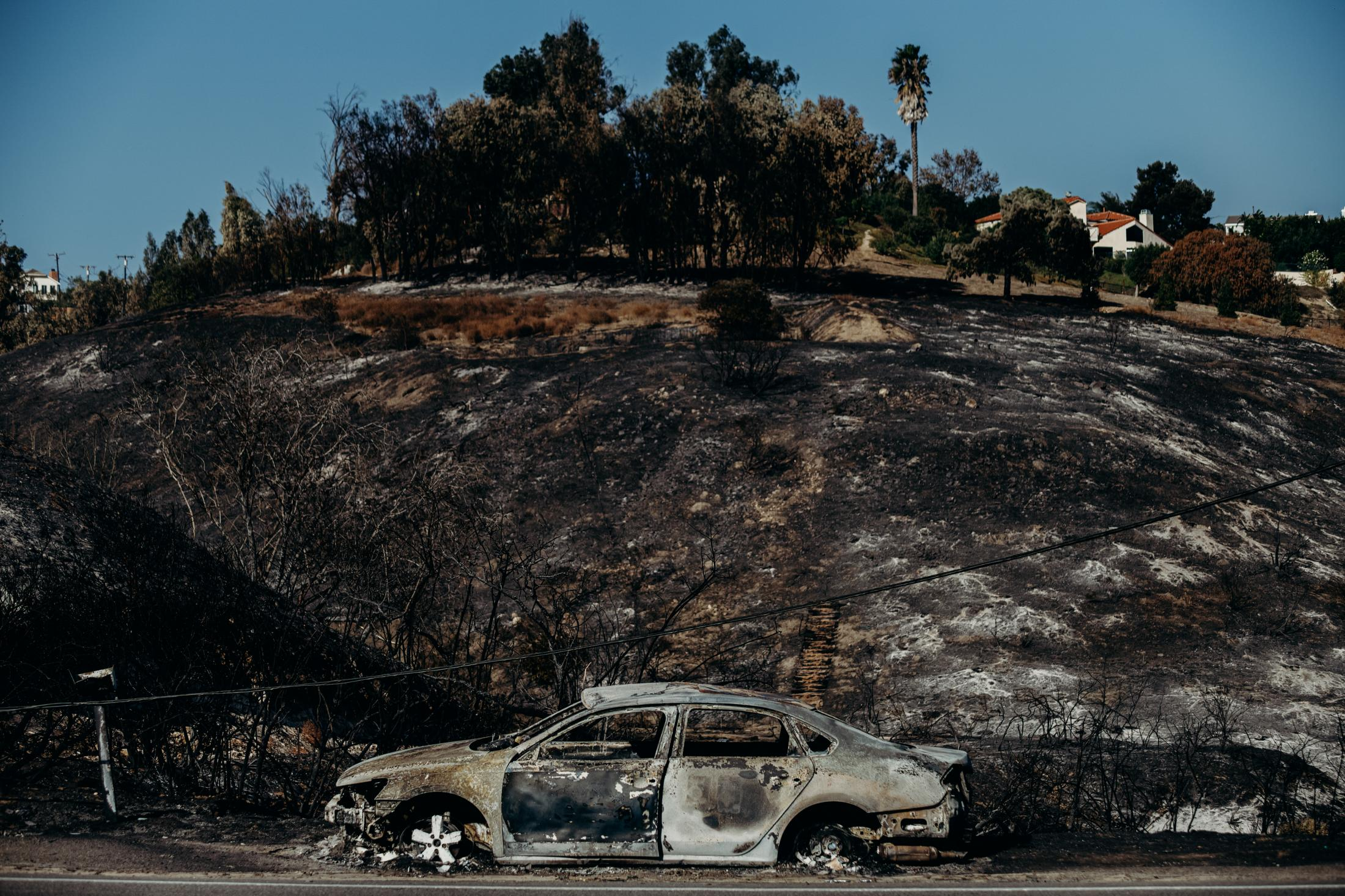 Three people reported to have died in the blaze, and over a quarter-million evacuated. A vehicle left on the side of the road is destroyed by a dangerous wildfire.