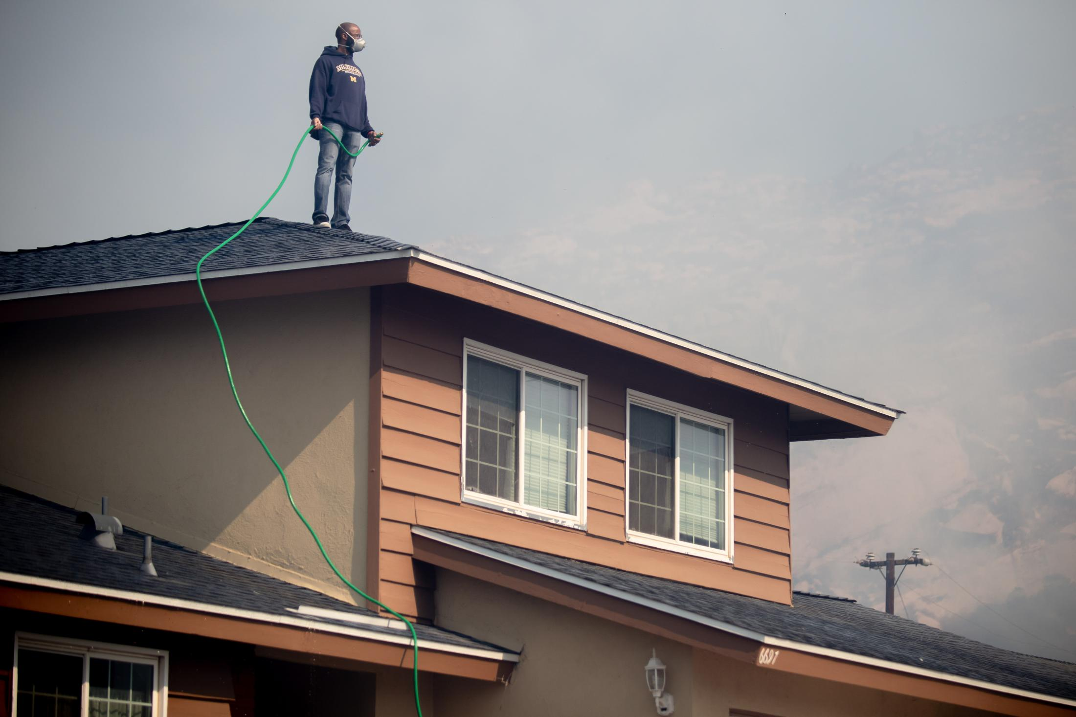 A resident stands on his roof with a garden house trying to water down his house to protect the home from the incoming wildfire.
