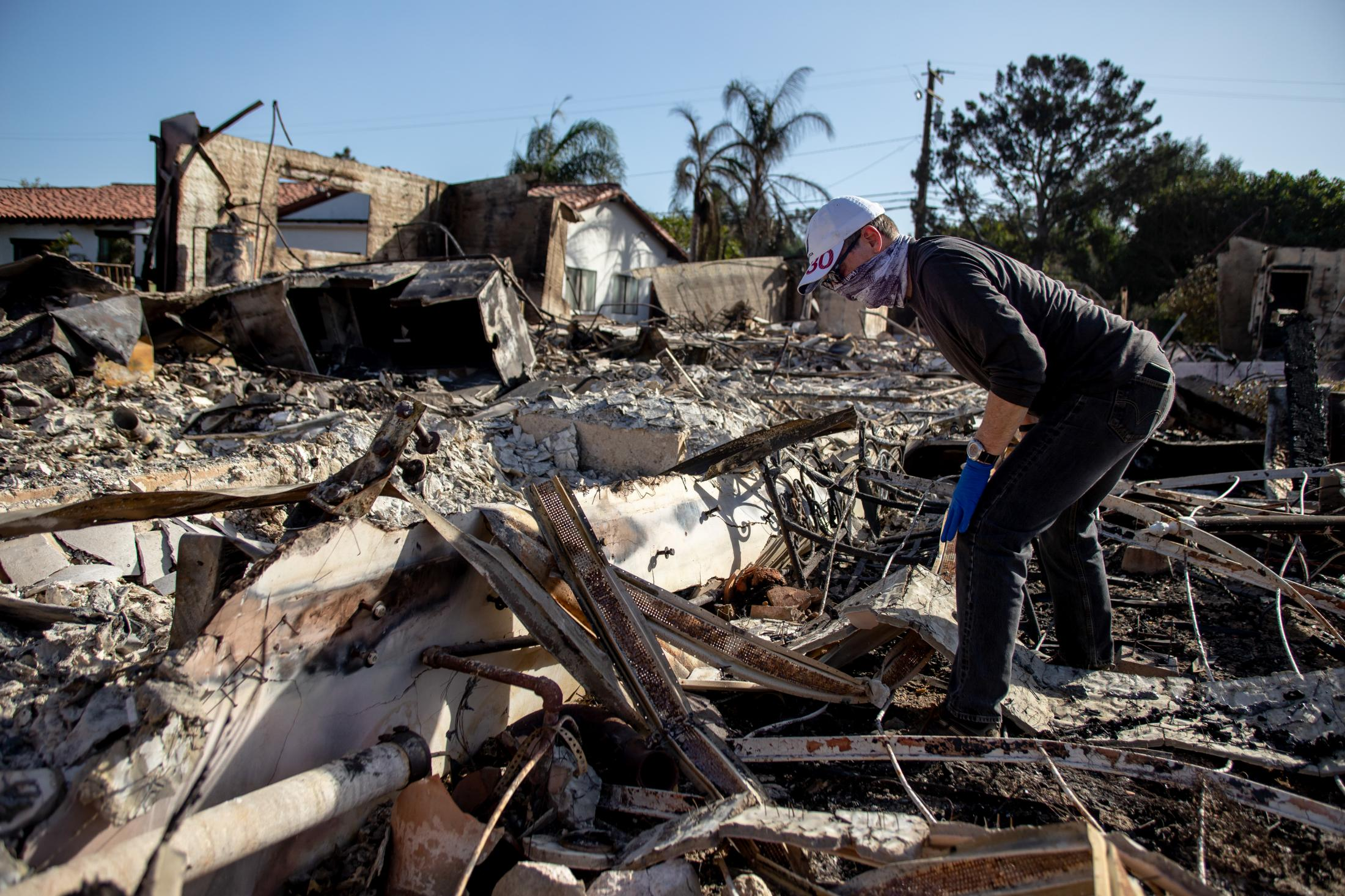 A man looks through the rubble of his home after it fell from a violent wildfire.