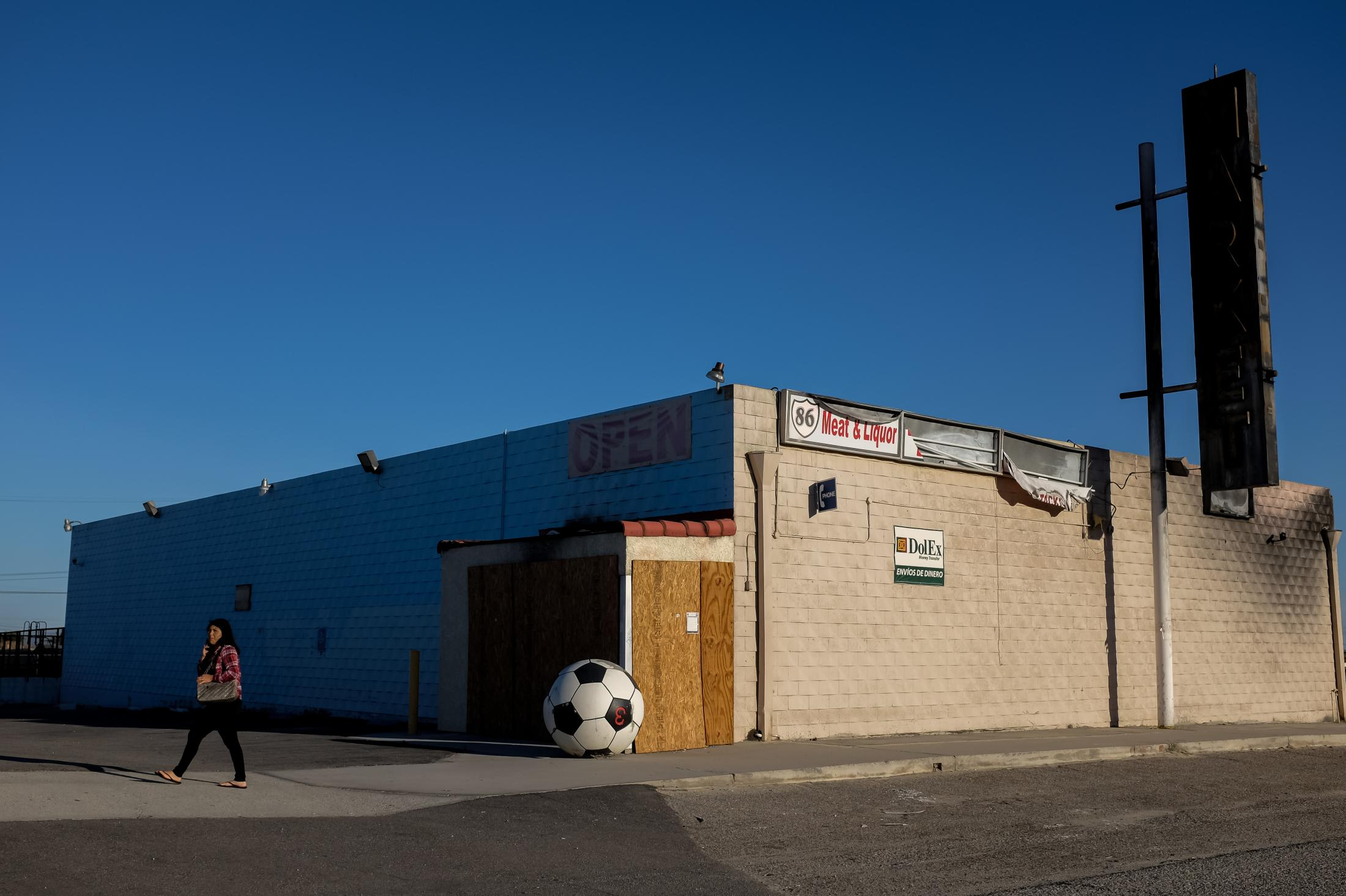 2/19/16-California - A woman walks past an abandoned sports supplies store in Niland, CA, the closest town near Slab City.