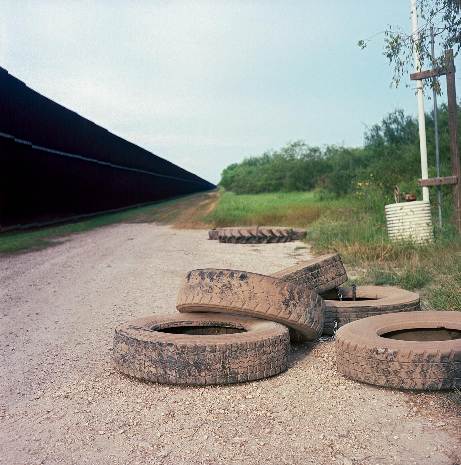 Brownsville, TX - OCTOBER 16, 2020: Old tires at the U.S.-Mexico border fence. Border agents hitch old tires to the backs of their patrol units and drag them across dirt roads paralleling the border in order to clear footprints to determine a timeline of crossings.