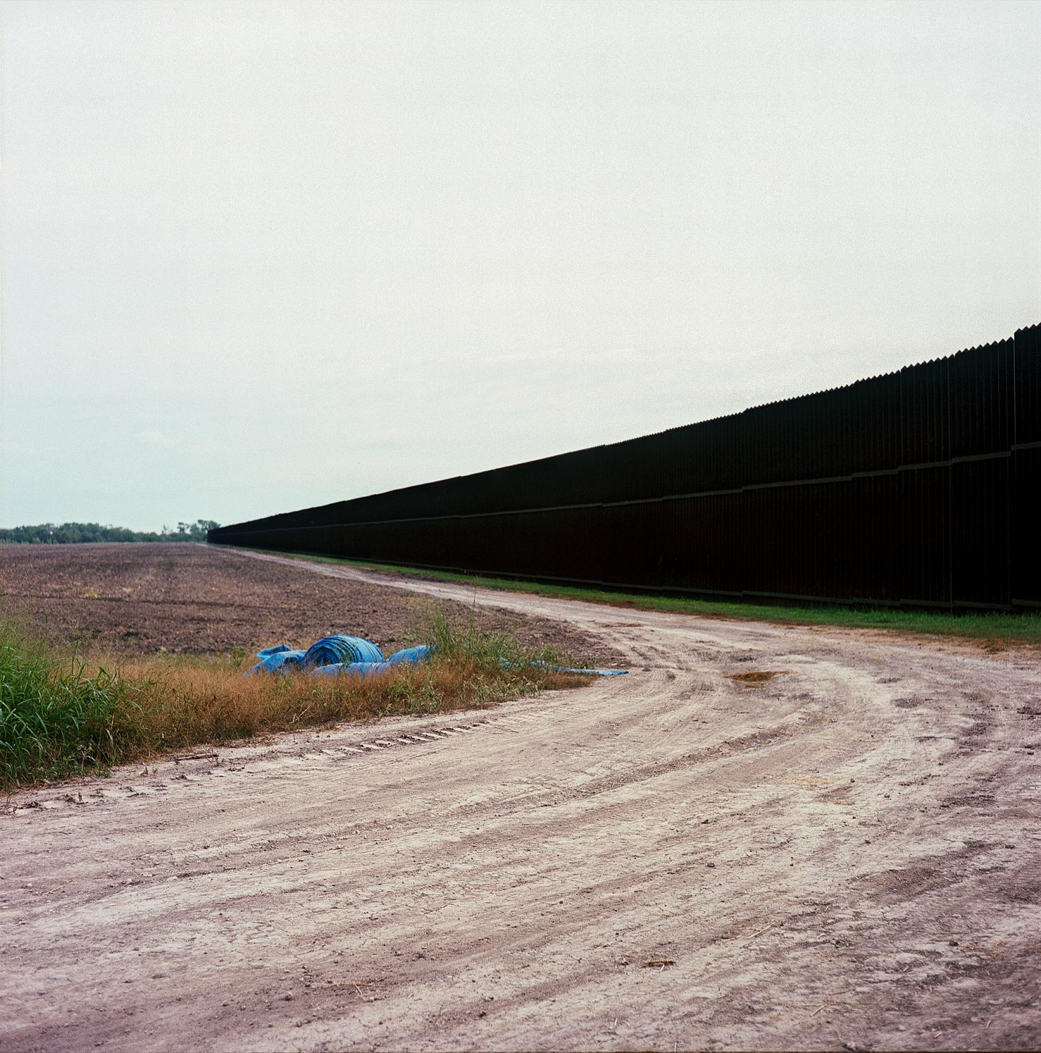 Brownsville, TX - OCTOBER 16, 2020: A dirt road paralleling the U.S.-Mexico border fence.