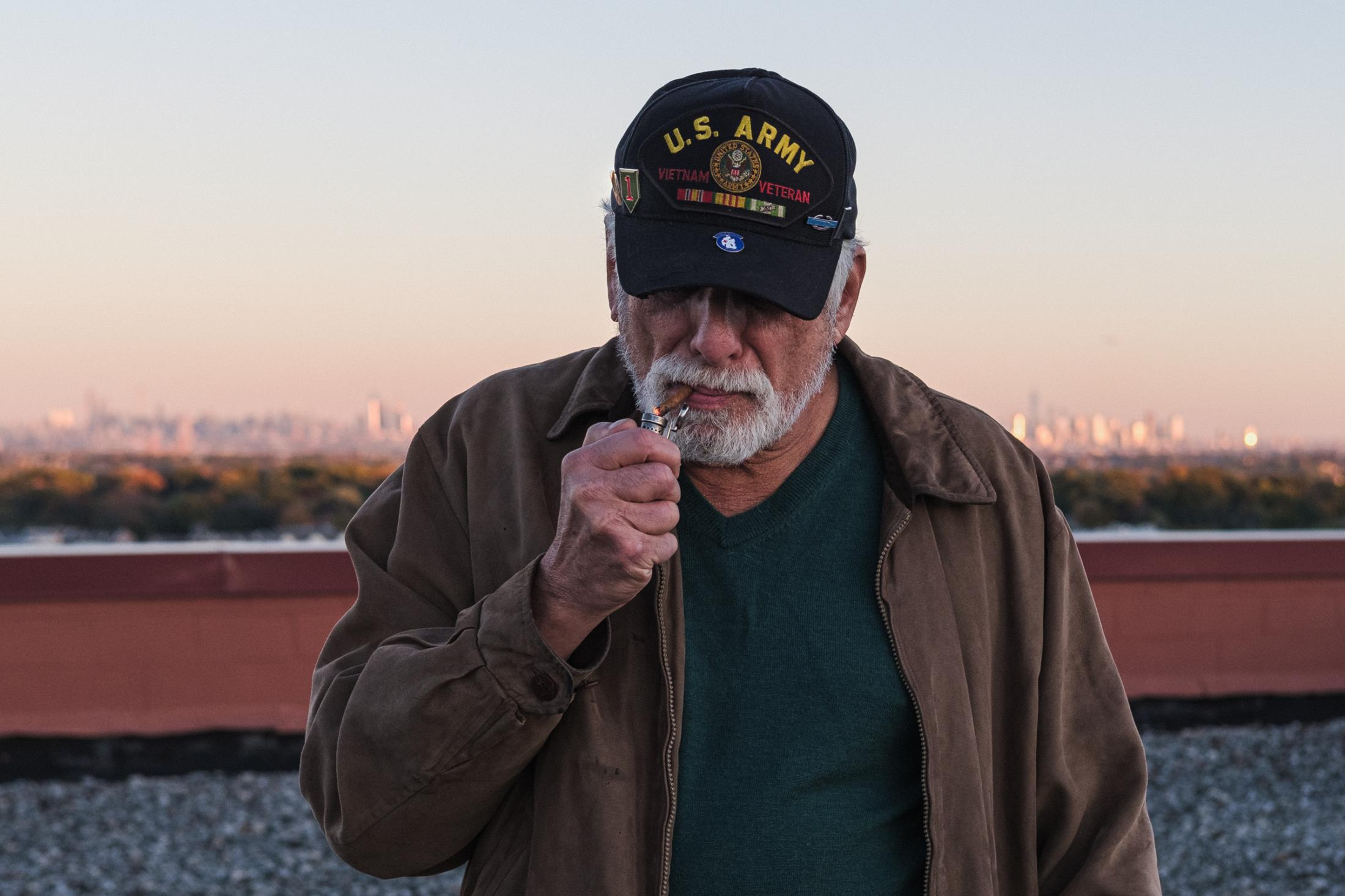 "Montclair, New Jersey. October 30, 2018. Lighting a cigar, Gene describes his experience in Vietnam. ""A scary moment was when I was promoted to platoon leader in the middle of a firefight."""
