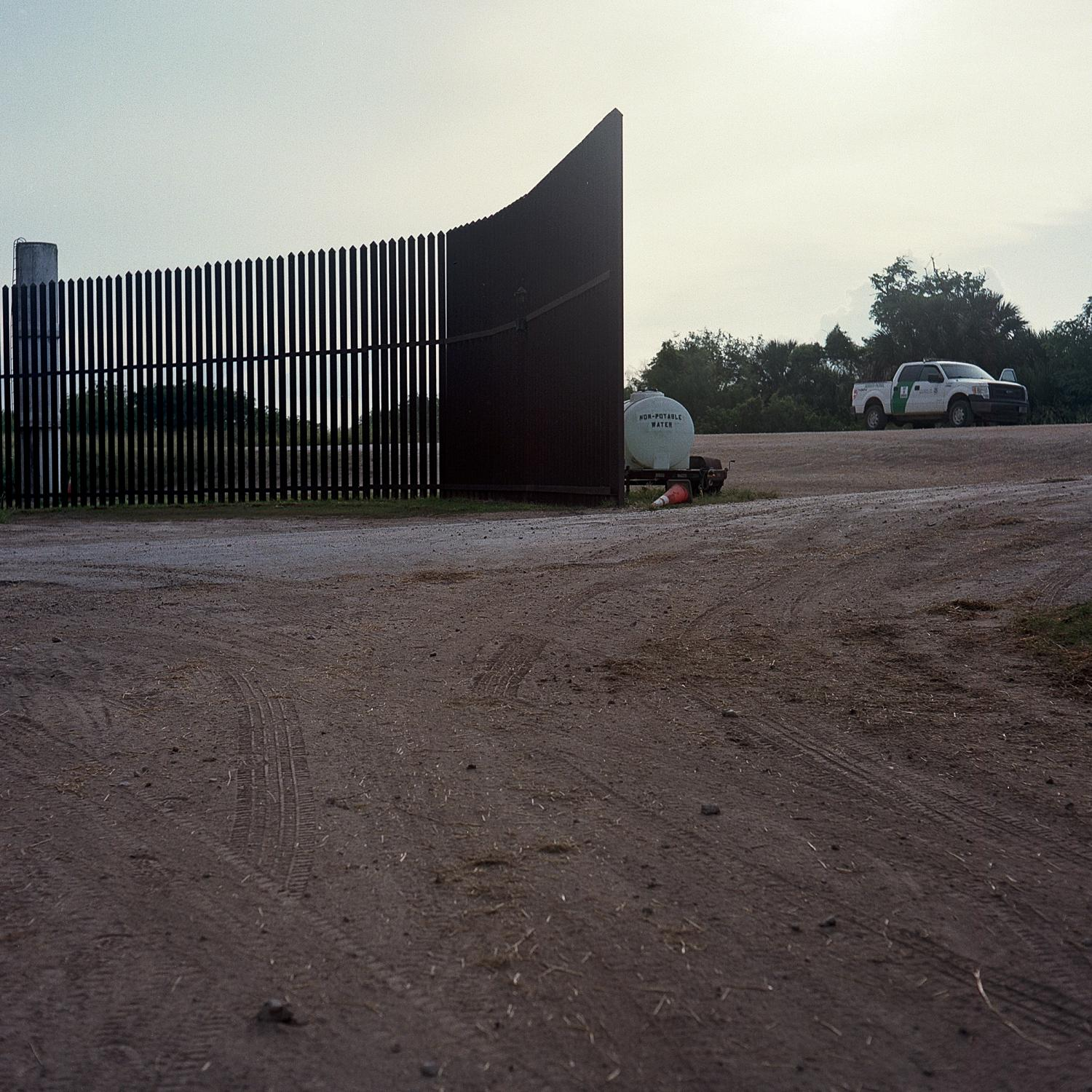 Brownsville, TX - OCTOBER 16, 2020: This part of the U.S.-Mexico border fence is located less than a mile away from the Rio Grande. At a distance, a Border Patrol truck.