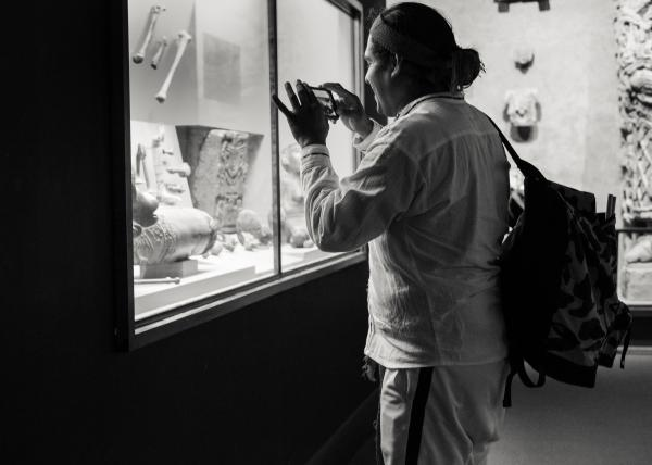 New York City, NY - October 8, 2018. Indigenous Peoples Day, 2018. 3rd Anti-Columbus Day Tour at American Museum of Natural History. David from Semillas Collective documenting a museum exhibit. Credit: Andres Guerrero