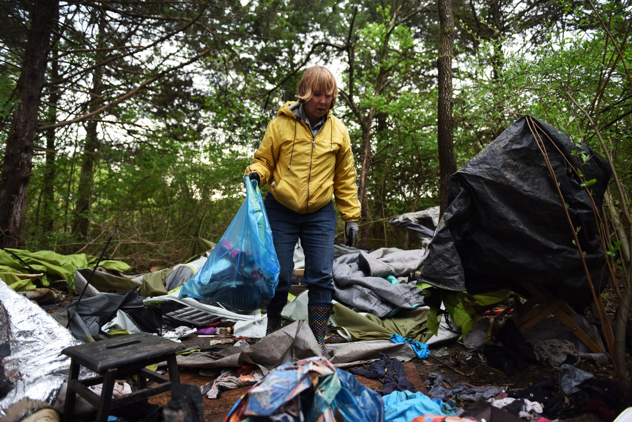 Flo Osborn steps through a homeless campsite in Columbia. Osborn was among a group of volunteers who led the effort to clean up abandoned campsites. A mix of volunteers pitched in, including a school board candidate, the John Brown Gun Club, a city councilman, members of Operation Safe Winter and some of the community's unhoused neighbors.