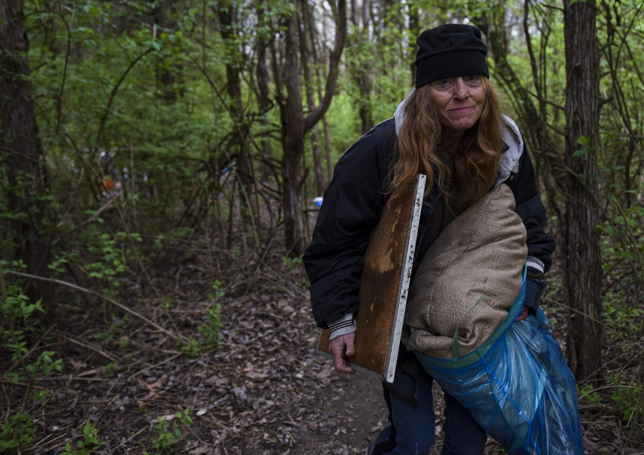 """Volunteer Diana Welch(CQ) carries some items out of the abandoned campsite on Saturday, April 11, 2020, in Columbia. Welch said the homeless have to struggle with everything from finding a place to lay their head at night to getting proper medical care. Welch broke her arm in an accident. """"Yeah, I don't have insurance so it is still broken,"""" Welch said. """"I can't imagine they'd be much help if I got sick from the coronavirus either."""" Samantha Waigand/Missourian"""