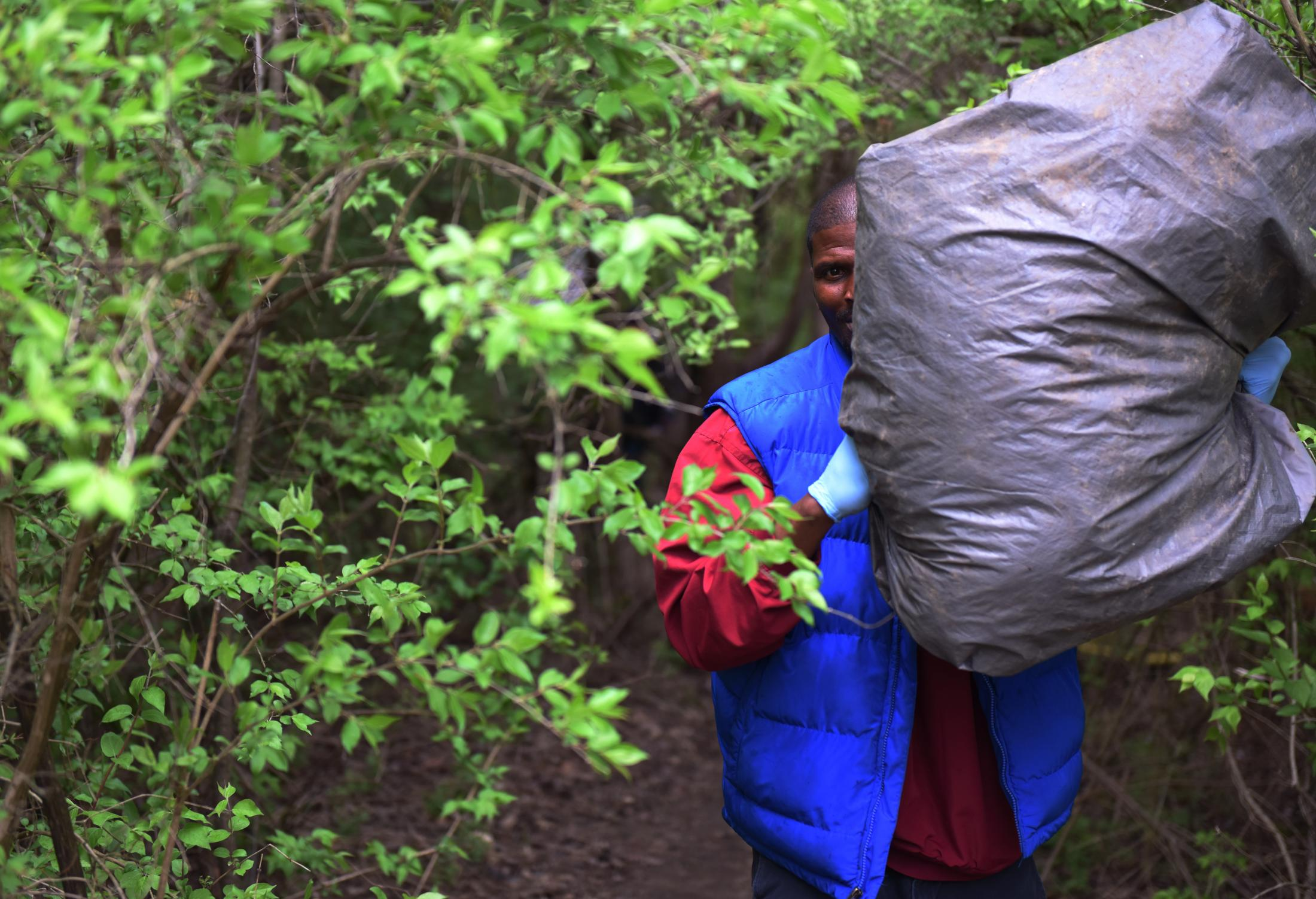 """A volunteer who goes by Kee carries trash from an abandoned campsite April 11. Kee said he doesn't define himself as homeless because his home is wherever he is. """"I think the responsibility falls on us as a community,"""" Kee said. """"Every last one of us has the power to change our circumstances. People shouldn't have to live like this."""""""
