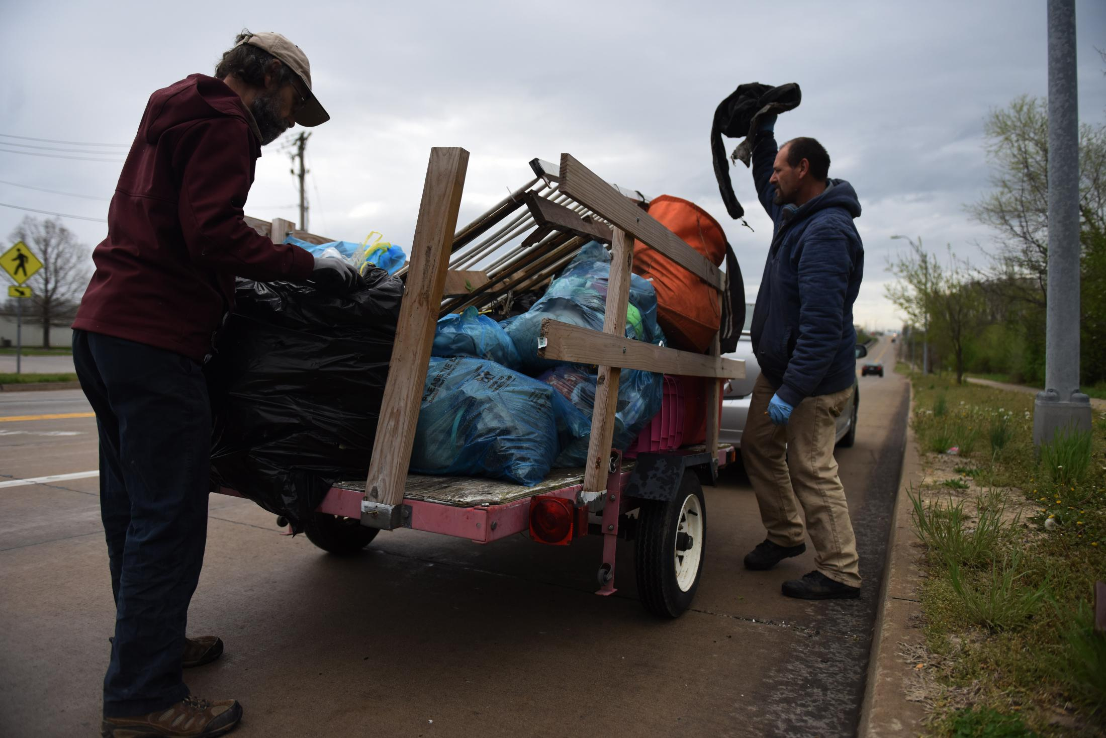 """John Trapp, who organized a cleanup of abandoned homeless camps, carries a box of trash to a trailer April 11. Trapp said the cleanup emerged from an effort to find the homeless a place to sit out the pandemic. """"Everyone deserves to have a place to feel safe."""""""