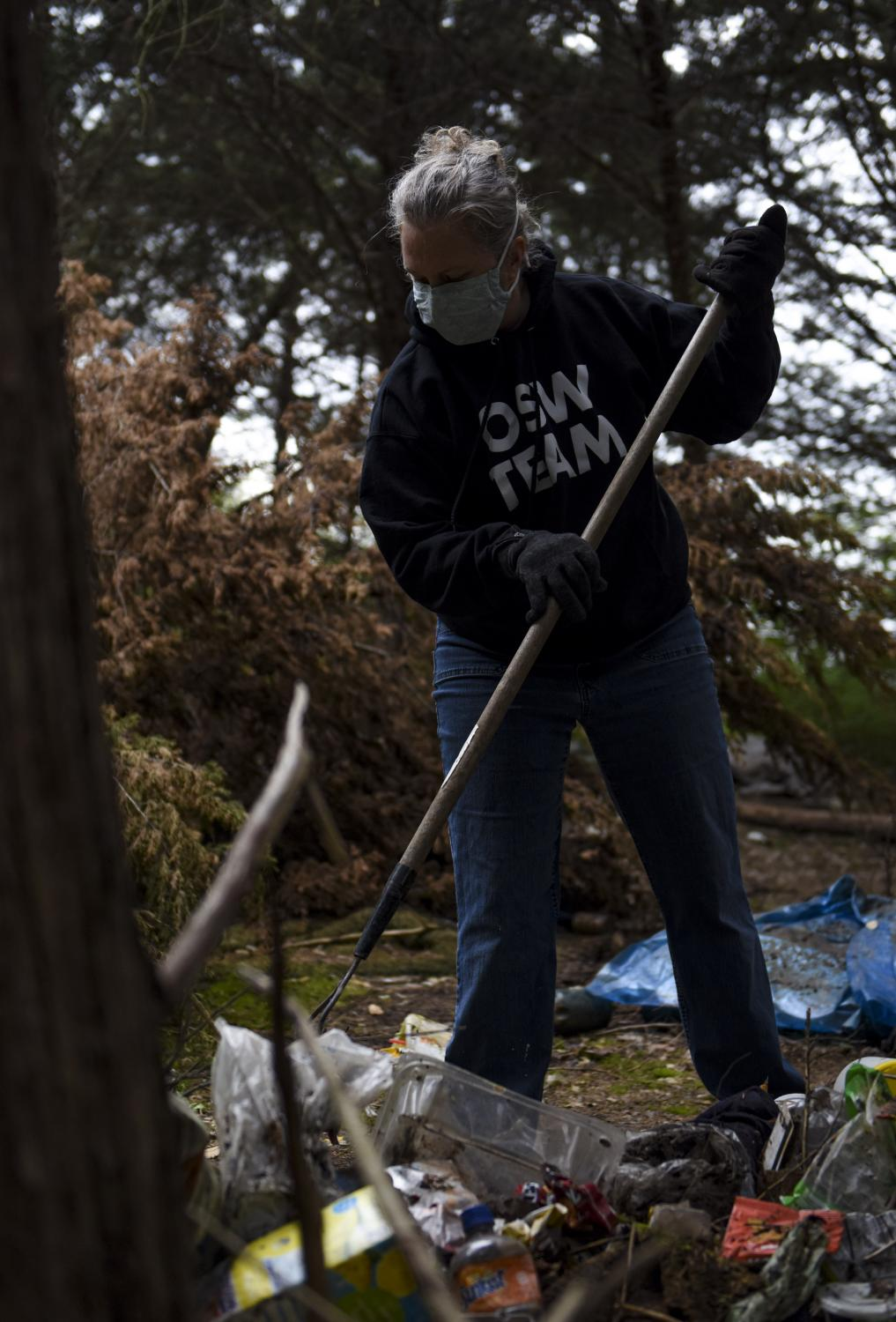 """Community volunteer Dawn Finney rakes a pile of garbage at the abandoned campsite on Saturday, April 11, 2020, in Columbia. Finney said it is hard to see people having to live like this. """"When I first saw the site, it was like a punch in the stomach,"""" she said. """"But it's not like these people have trash services."""""""