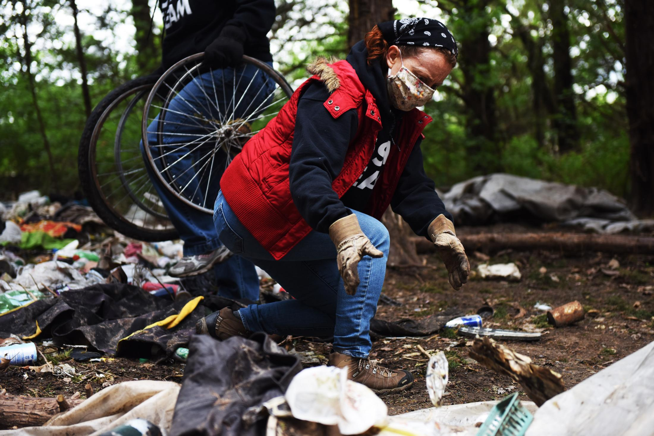 """Volunteer Renee Maxwell picks up trash April 11 in an abandoned campsite in Columbia. Maxwell regularly volunteers with Operation Safe Winter. """"We just want to help in whatever way we can,"""" she said."""