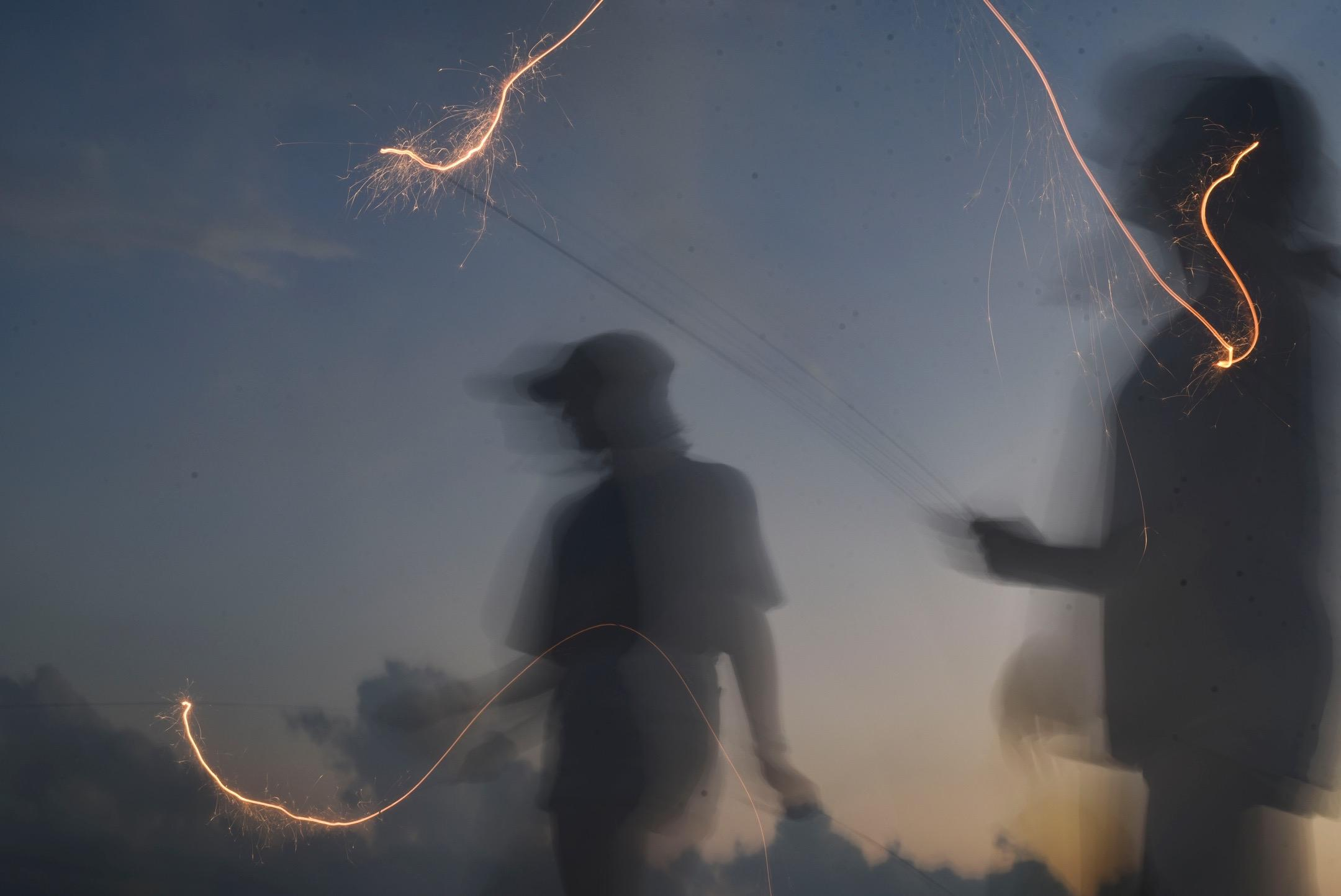 Camille McManus and Christina Long wave sparklers July 4, 2020 in Rich Hill, Mo.