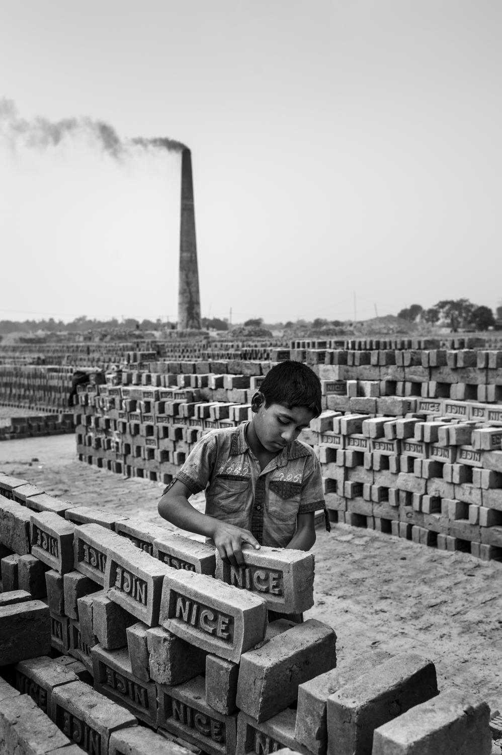 Bangladesh, Rajshahi, Hari Shankarpur. January 2013 Hasan is ten years old and works at �Nice� brick factory. His work is to stack bricks: for every 1000 bricks he stacks, he gets 20 Taka. In a good day of work he can earn up to 100 Taka (aprox 1US$). Hasan is forced to work to help support his family. Hasan is still going to school, he is in class six. Although the law prohibits child labour, the practice is consistent throughout the region. Enforcement of existing laws is inadequate. Child labour is technically illegal but extremely widespread. Driven by poverty, it is often parents who are forced to push their children into work at an early age. (please note all the real names of the children is this story have been changed to protect their identity)
