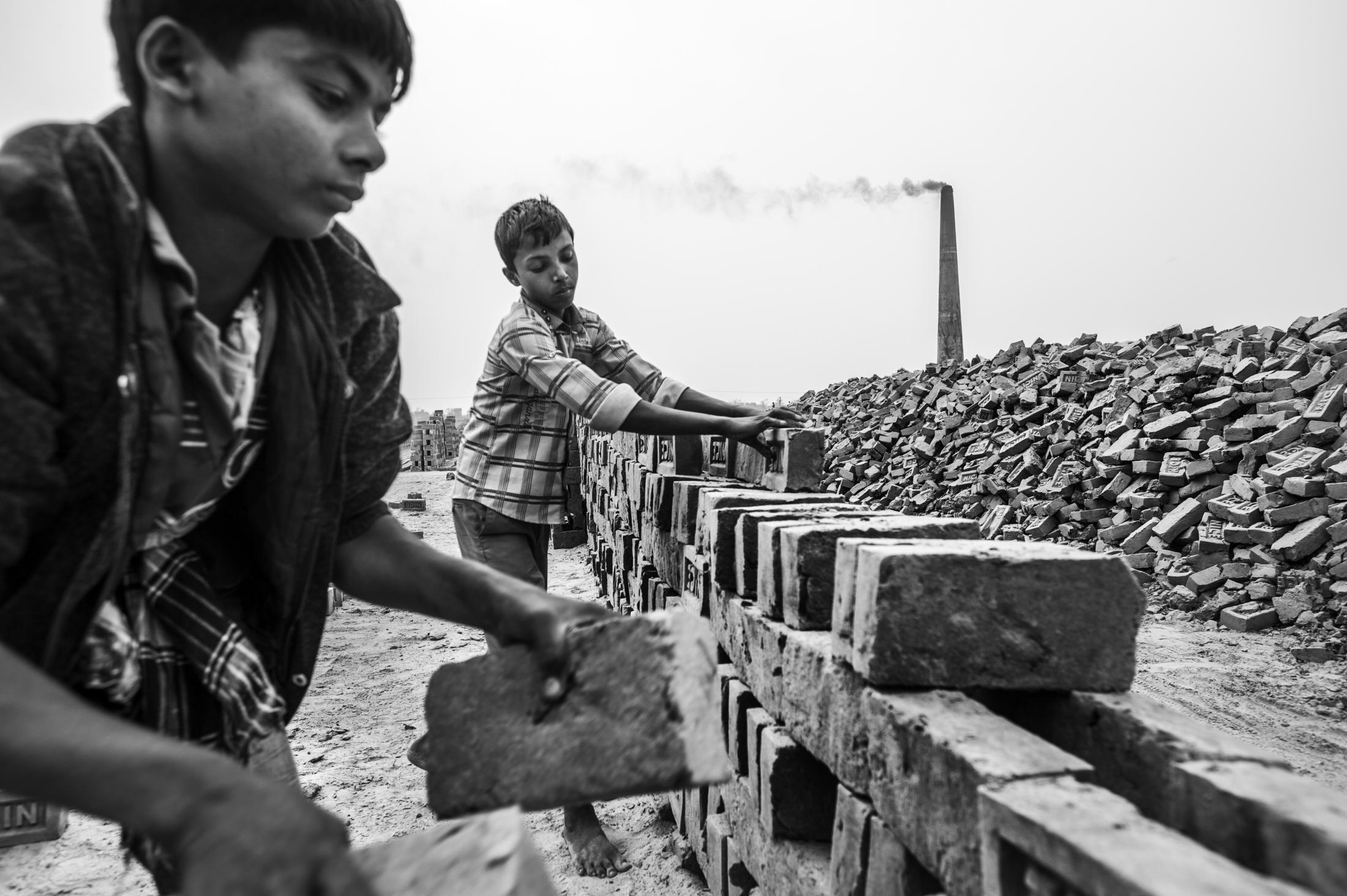Rasel (right) and Mohamed work at �Nice� brick factory. Their work entails shifting and carting sand from one place to another, as well as stacking bricks. On a good day they can earn up to 130 Taka a day. They are forced to work to help support their families. Although the law prohibits child labour, the practice is consistent throughout the region. Enforcement of existing laws is inadequate. Child labour is technically illegal but extremely widespread. Driven by poverty, it is often parents who are forced to push their children into work at an early age. (please note all the real names of the children is this story have been changed to protect their identity)