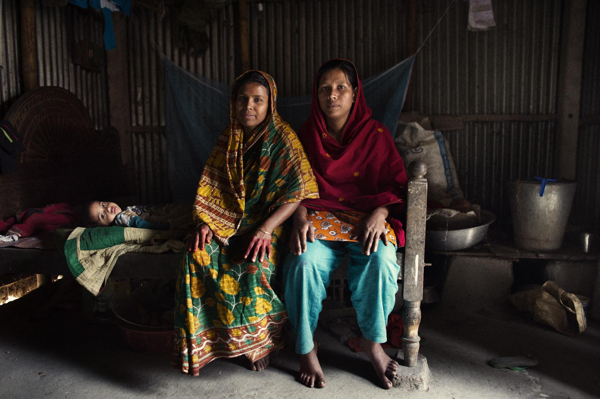 Bangladesh, Dhaka, Narayon Gong, Katabo village. January 2012 Portrait of Salma (red), she is twenty-four years old, and got her first microcredit two years ago, she makes Shari (traditional clothes for women) together with her cousin Muslima (green) twenty-two years old, she has one son and one daughter (in the picture) two and a half years old. Muslima got her first microcredit three years ago.