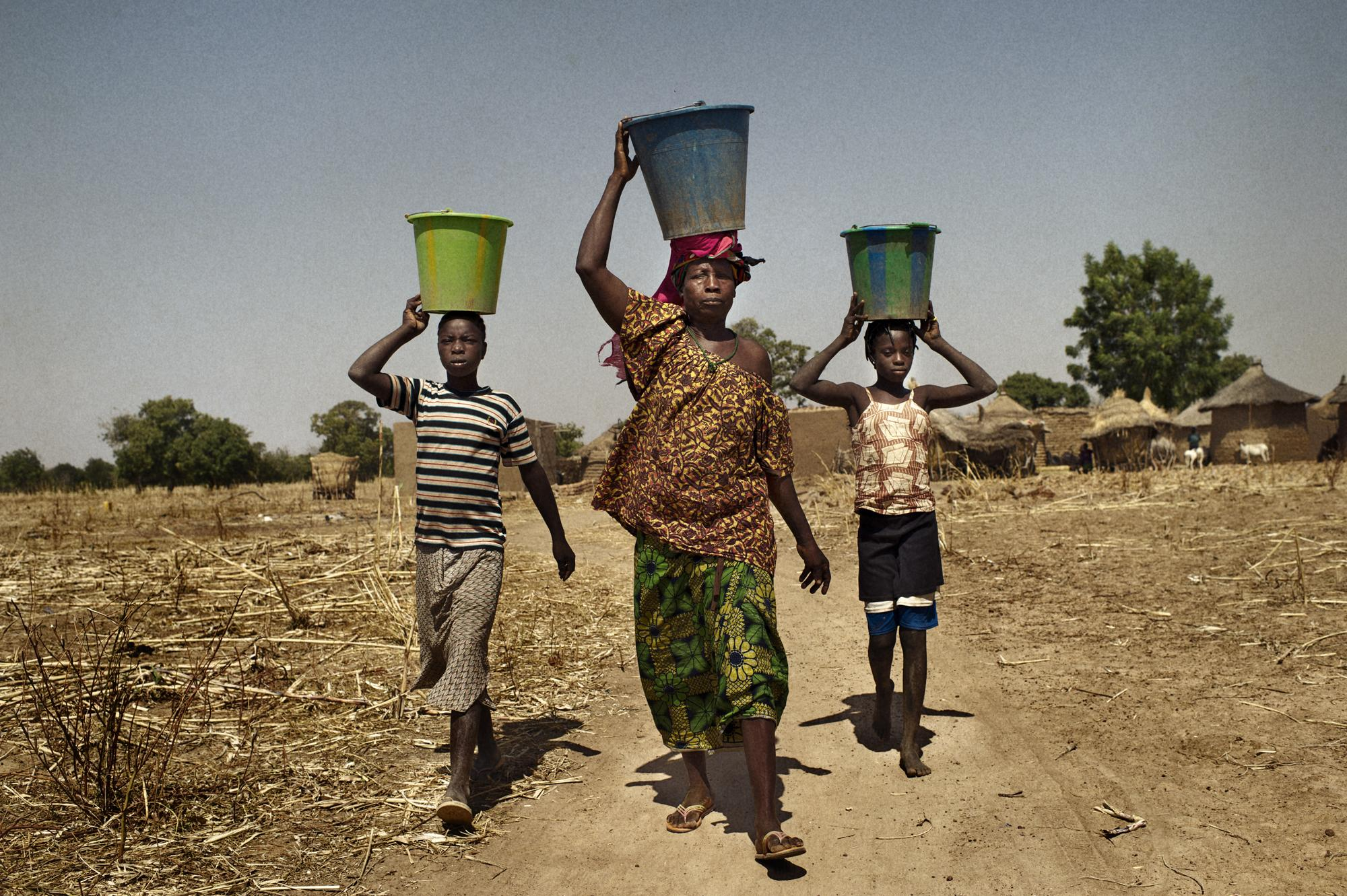 """Burkina Faso, Moyaorgo. November 2011. Abzeta Derra with her grand children going to fetch water, Azbeta makes a living from selling """"Soumbala"""" at the market. Abzeta is sixty-nine years old and has nine children. She started her first microcredit in April 2011with GASCODE program (Groupe d'Appui en Santé, Communication et Developpement) a local organization that supports poor women."""