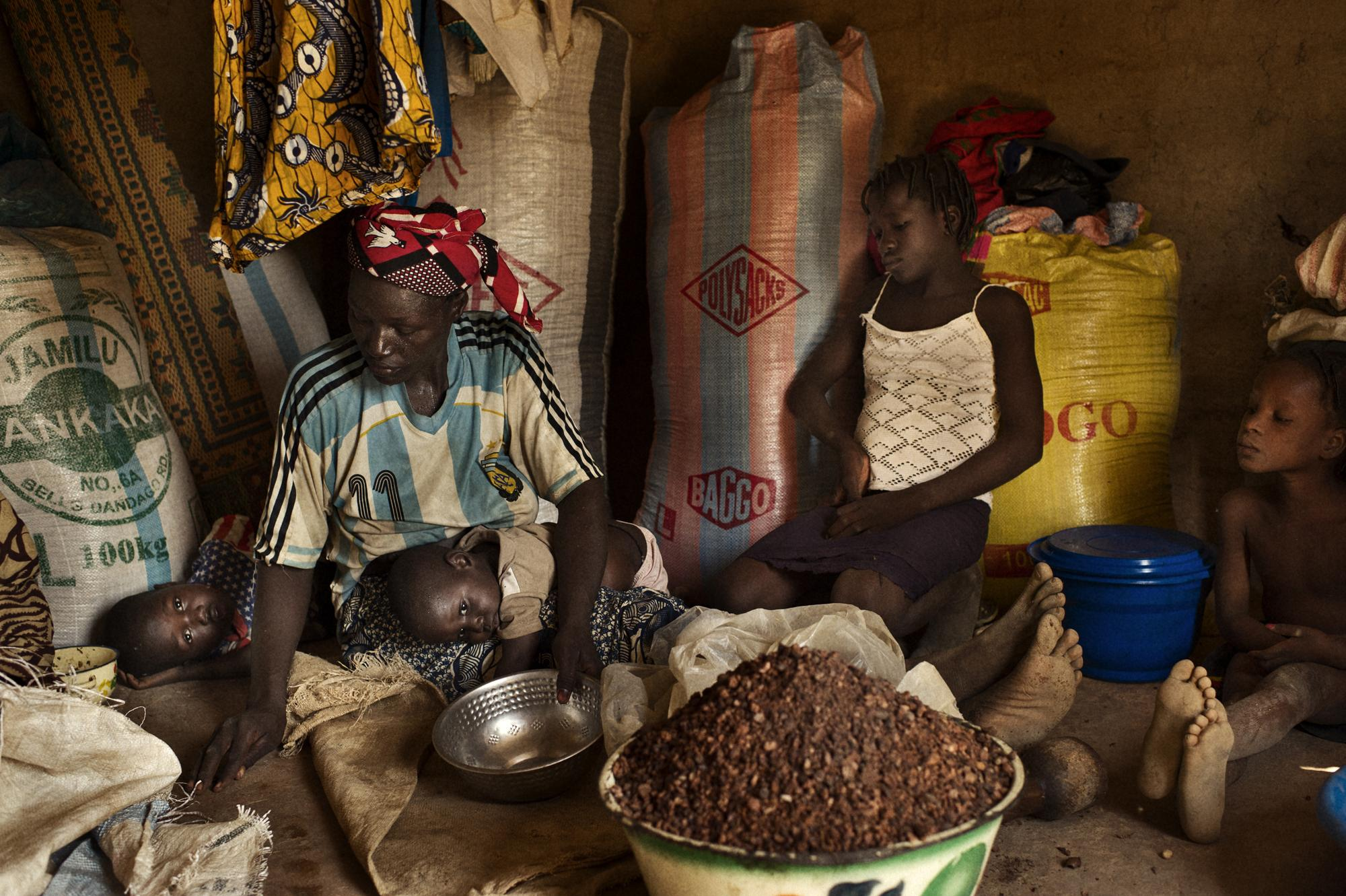 """Burkina Faso, Moyaorgo. November 2011. Aminata Bande is twenty-nine years old, she has three children and makes """"Karite butter"""". She lives and works with her mother Salamata. She started her first microcredit in April 2011with GASCODE program (Groupe d'Appui en Santé, Communication et Developpement) a local organization that supports poor women."""