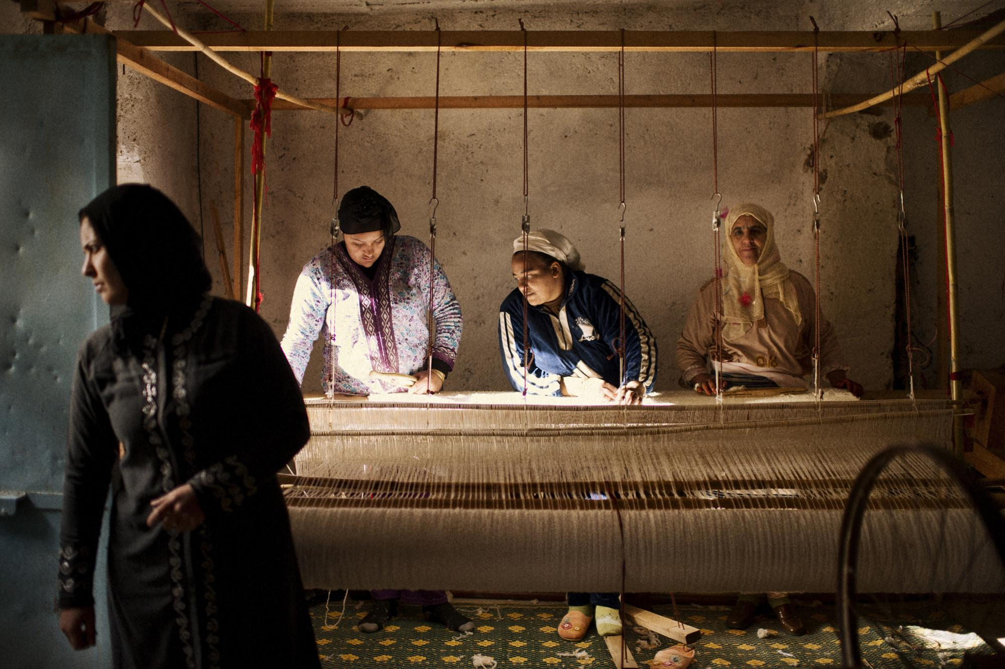 Morocco, Ain-Leuh. November 2011. Khadija Elabdi (second right) is Thirty seven years old, she started her first microcredit ten months ago. She makes fabrics and rugs, with her two friends Rachidi and Khadija.