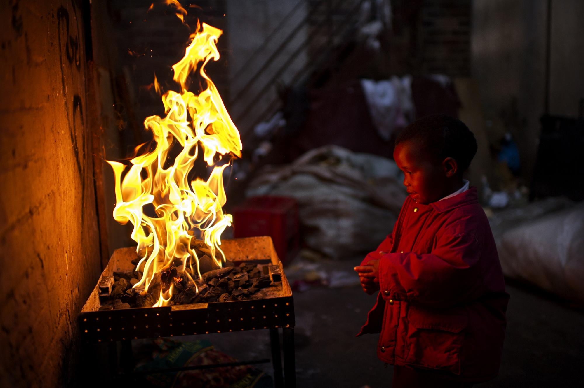 Johannesburg, South Africa. June 2011. Elephant house slum building. A kid next to the fire.