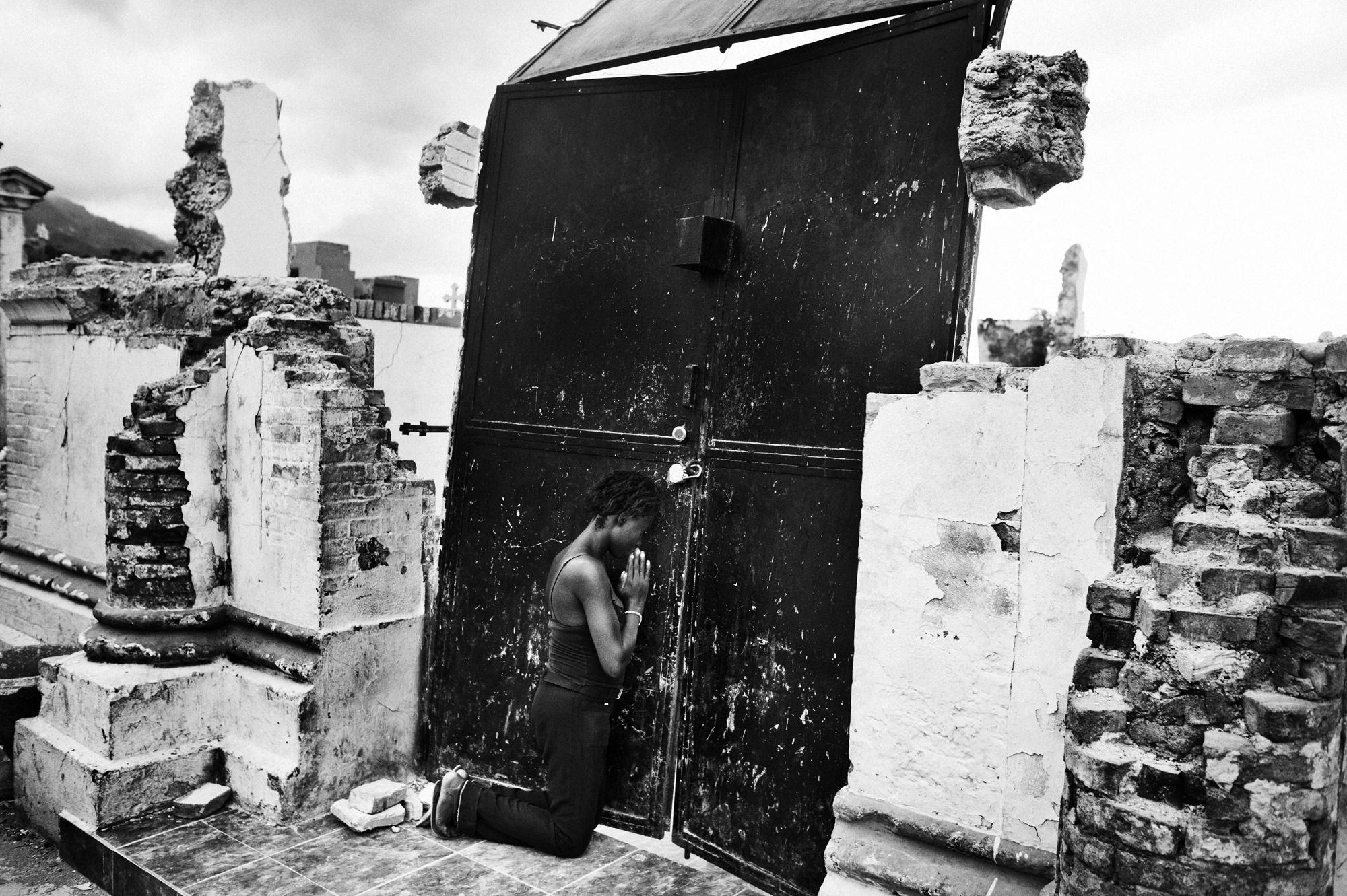 Port au Prince. June 2010. A woman praying at the door of the destroyed church of the Port au Prince cementery.