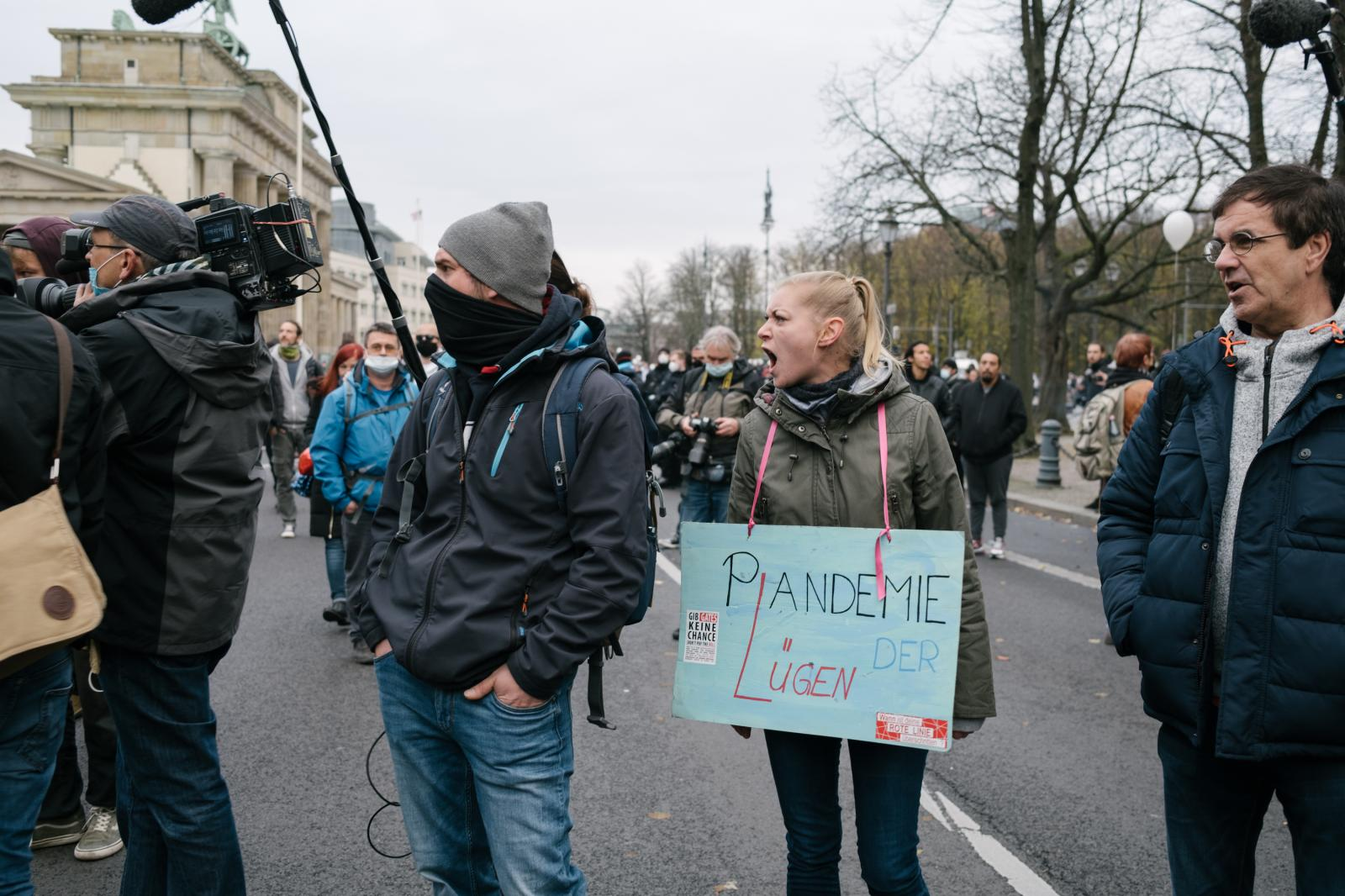 "A woman shouts at a camera team holding interviews wearing a sign ""Pandemic of Lies""."