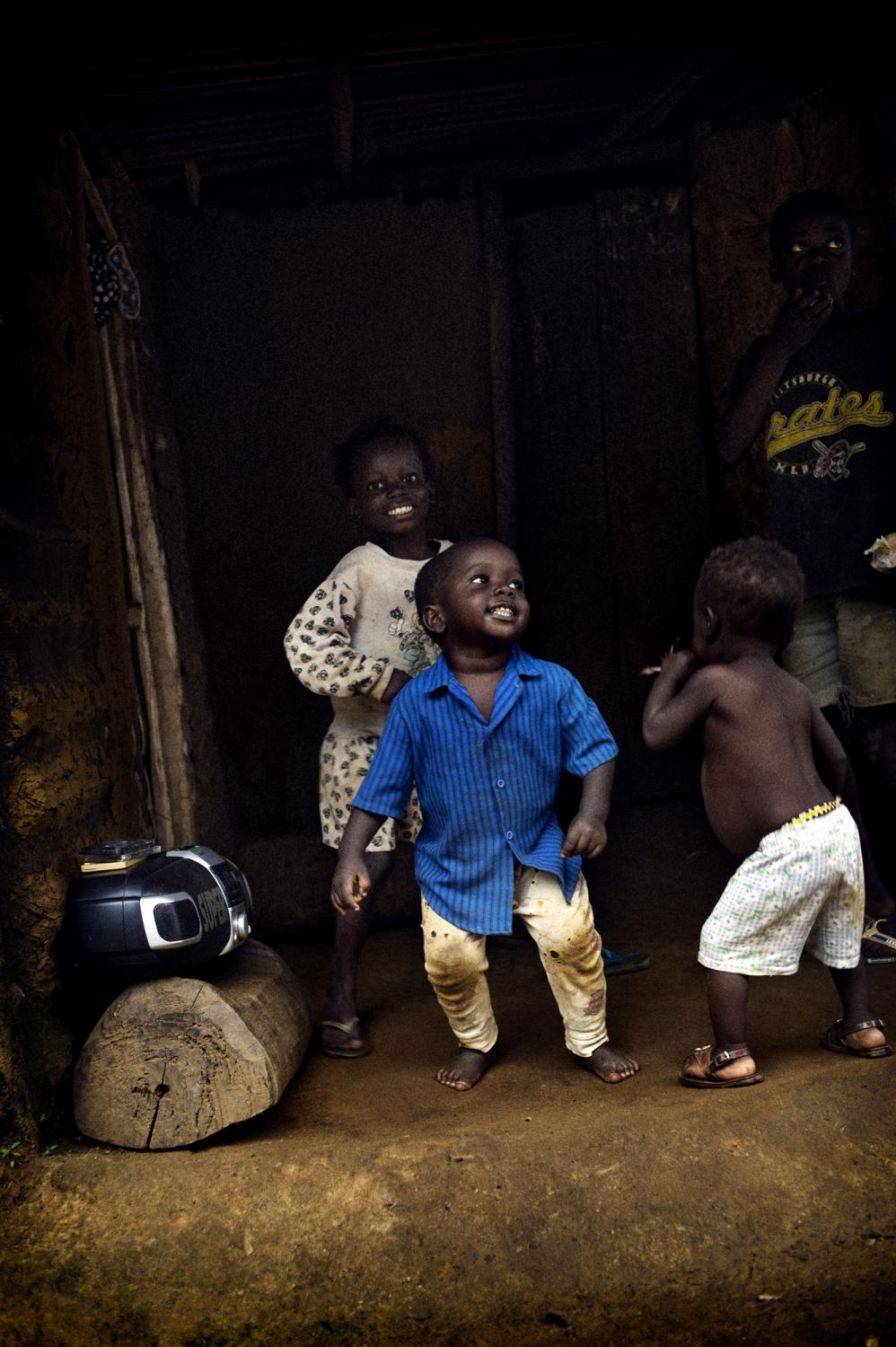 Liberia, Bunny's Town. October 2008. Children dancing with an old radio.